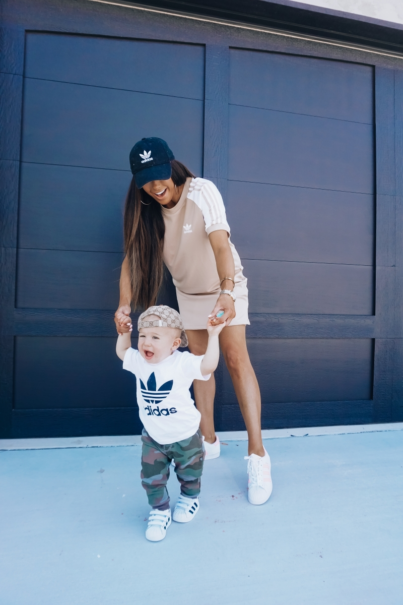 best #nsale kids outfits, cute baby boy fashion adidas, emily ann gemma, baby boy fashion fall pinterest 2018 | Cute Baby Boy Outfit by popular US fashion blog, The Sweetest Thing: image of a mom and her baby wearing Nordstrom adidas Trefoil Baseball Cap ADIDAS ORIGINALS, Nordstrom Caber Diamond Bracelet Watch, 35mm MICHELE, Nordstrom Trefoil Logo Tee ADIDAS ORIGINALS, Nordstrom Camo Knit Pants TUCKER + TATE, and Nordstrom baby Adidas shoes.