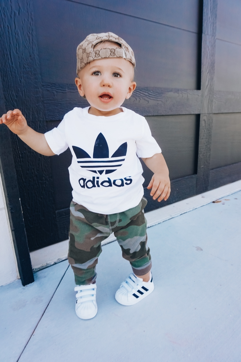 best #nsale kids outfits, cute baby boy fashion adidas, emily ann gemma, baby boy fashion fall pinterest 2018 | Cute Baby Boy Outfit by popular US fashion blog, The Sweetest Thing: image of a baby wearing a Nordstrom Trefoil Logo Tee ADIDAS ORIGINALS, Nordstrom Camo Knit Pants TUCKER + TATE, and Nordstrom baby Adidas shoes.