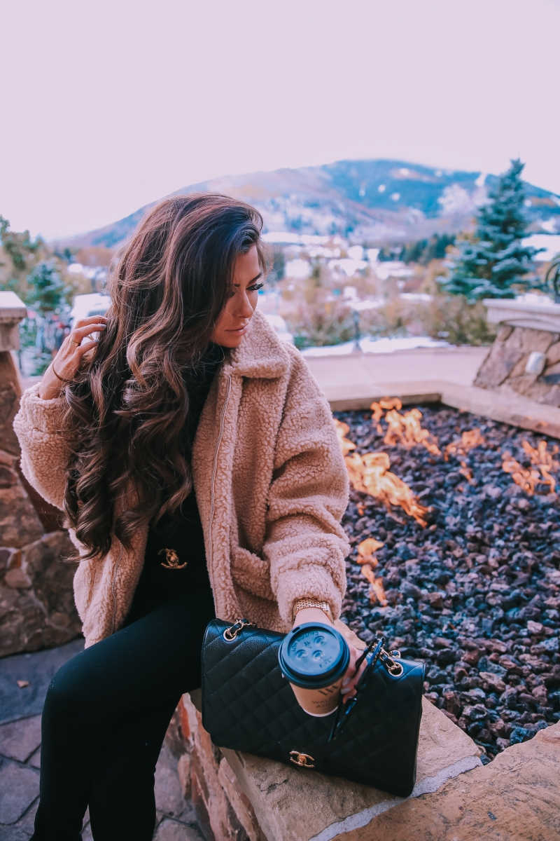 Fall fashion pinterest 2018, teddy bear coat outfit pinterest 2018, IAMGIA teddy coat, chanel belt outfit, park city travel fashion blogger, emily gemma blog, chanel classic black maxi-3 | I Am Gia Teddy Bear Jacket by popular US fashion blog, The Sweetest Thing: image of a woman standing outside next to a gas fire pit and wearing a Pixie Coat  I.AM.GIA brand: I.AM.GIA, H&M Ribbed Turtleneck Top, Nordstrom Florence Instasculpt Ankle Skinny Jeans DL1961, ShopBop Ash boots, H&M Large Earrings, Nordstrom Lip Cheat Lip Liner CHARLOTTE TILBURY, Chanel belt, Chanel purse, and Nordstrom MAC Matte Lipstick MAC COSMETICS.