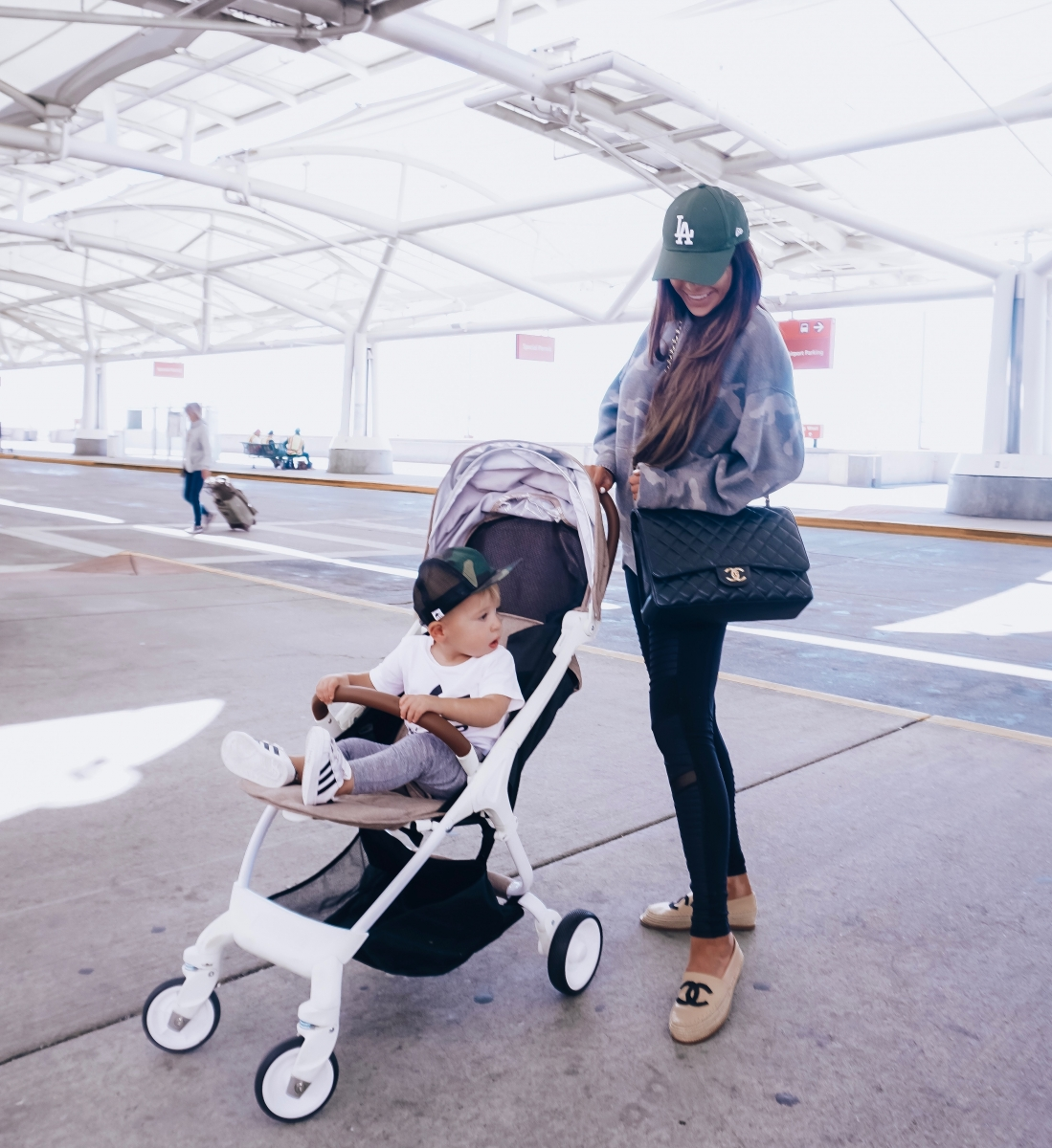 pinterest cute airport travel fashion outfit fall 2018, emily gemma travel style, stylish cute casual travel outfit idea 2018, travel stroller baby sing amazon, camo sweatshirt leggings travel outfit