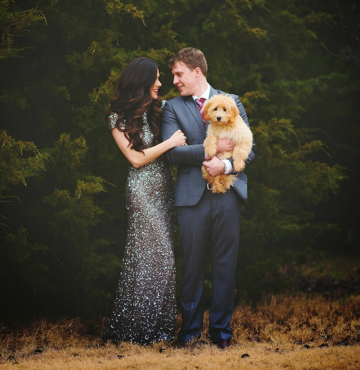 Sequin Leggings Outfit by popular US fashion blog, The Sweetest Thing: image of a woman wearing a silver sequin dress and standing next to her husband who is wearing a suit and holding their goldendoodle puppy.