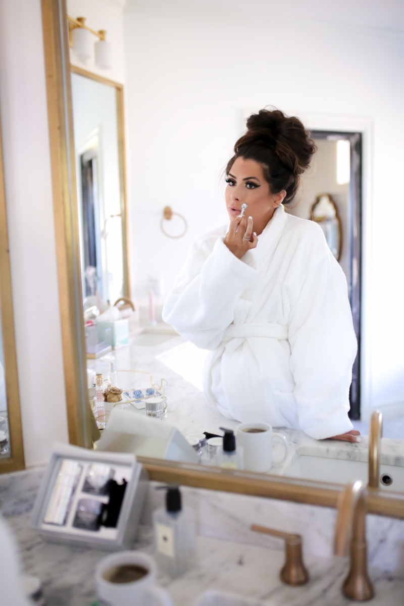 Elemis Pro Collagen Skin Care Line by Popular US beauty blog, The Sweetest Thing: image of a woman applying an Elemis Pro Collagen skin care product.