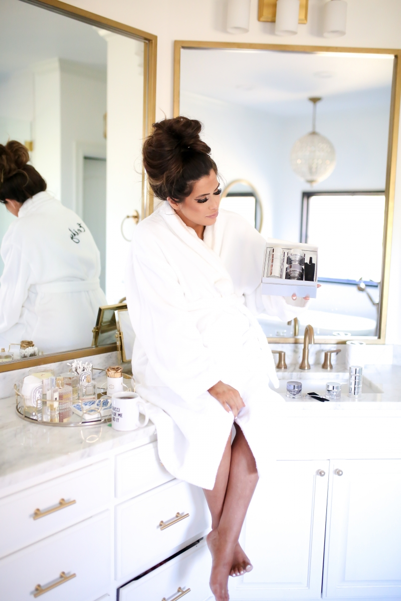 Elemis Pro Collagen Skin Care Line by Popular US beauty blog, The Sweetest Thing: image of a woman wearing a white bathrobe and sitting on her bathroom counter while holding some Elemis Pro Collagen skin care products.