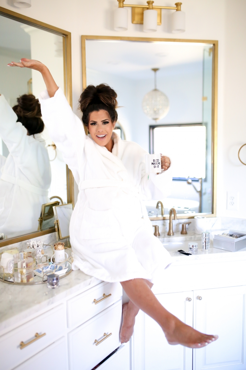 Elemis Pro Collagen Skin Care Line by Popular US beauty blog, The Sweetest Thing: image of a woman wearing a white bathrobe and sitting on her bathroom counter.