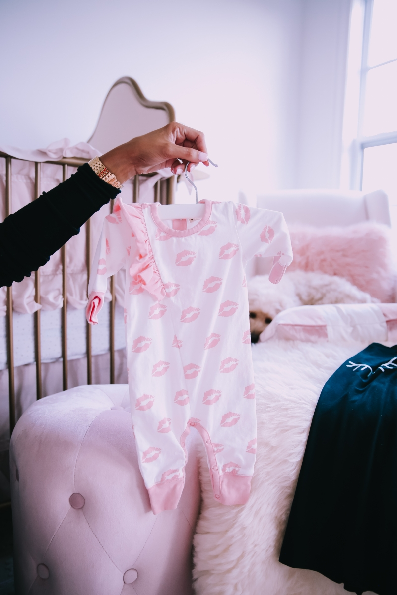 Emily Ann Gemma of The Sweetest Thing Blog in baby girl nursery. Favorite baby onesie.