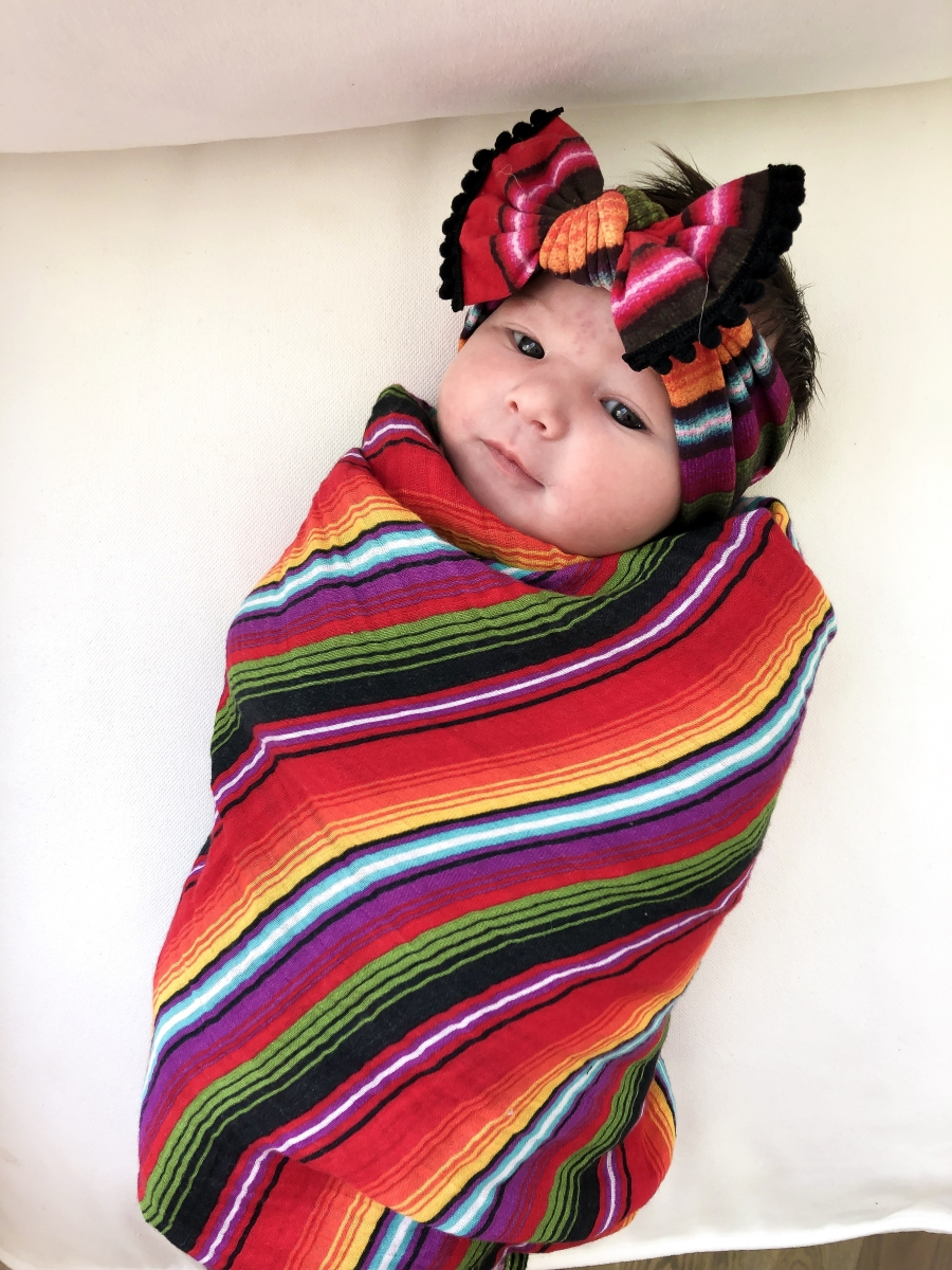 Emily Ann Gemma of The Sweetest Thing Blog with new baby. Colorful baby blanket and bow.