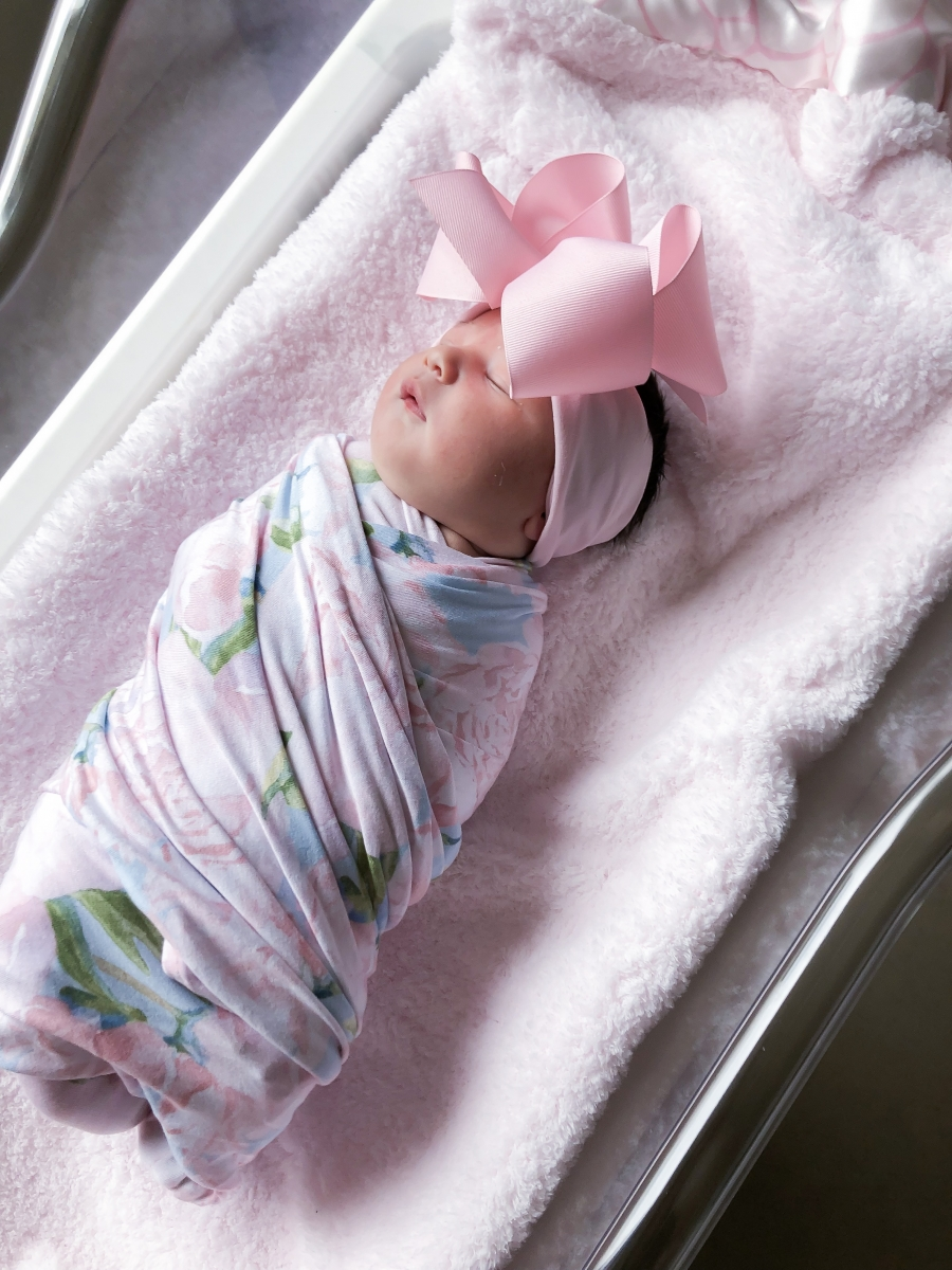 Emily Ann Gemma of The Sweetest Thing Blog with new baby. Cute baby bow and swaddling blanket.