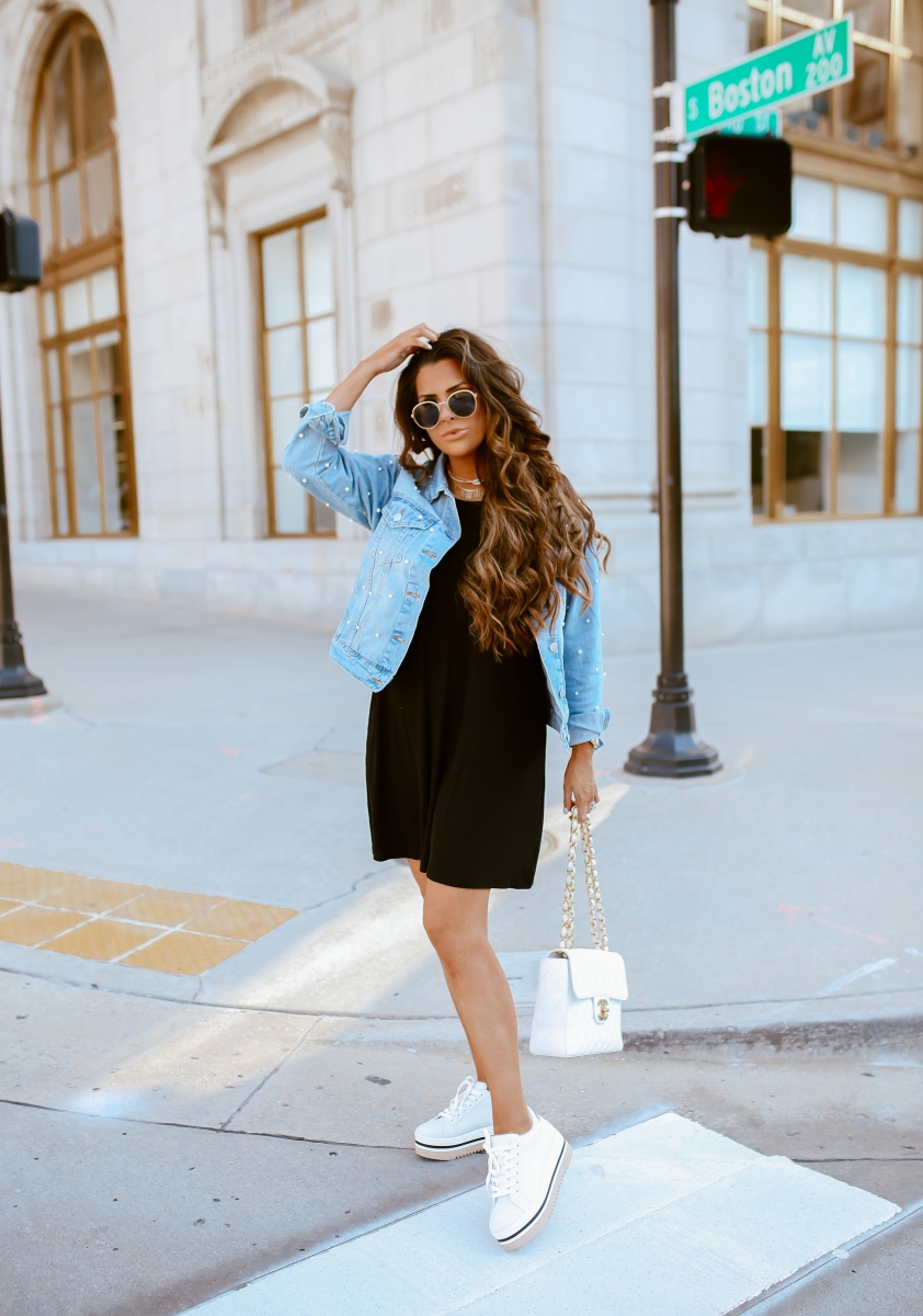 Emily Ann Gemma of The Sweetest Thing Blog in an under $40 black dress, pearl embellished denim jacket, white Chanel handbag, and platform tennis shoes from Steve Madden.