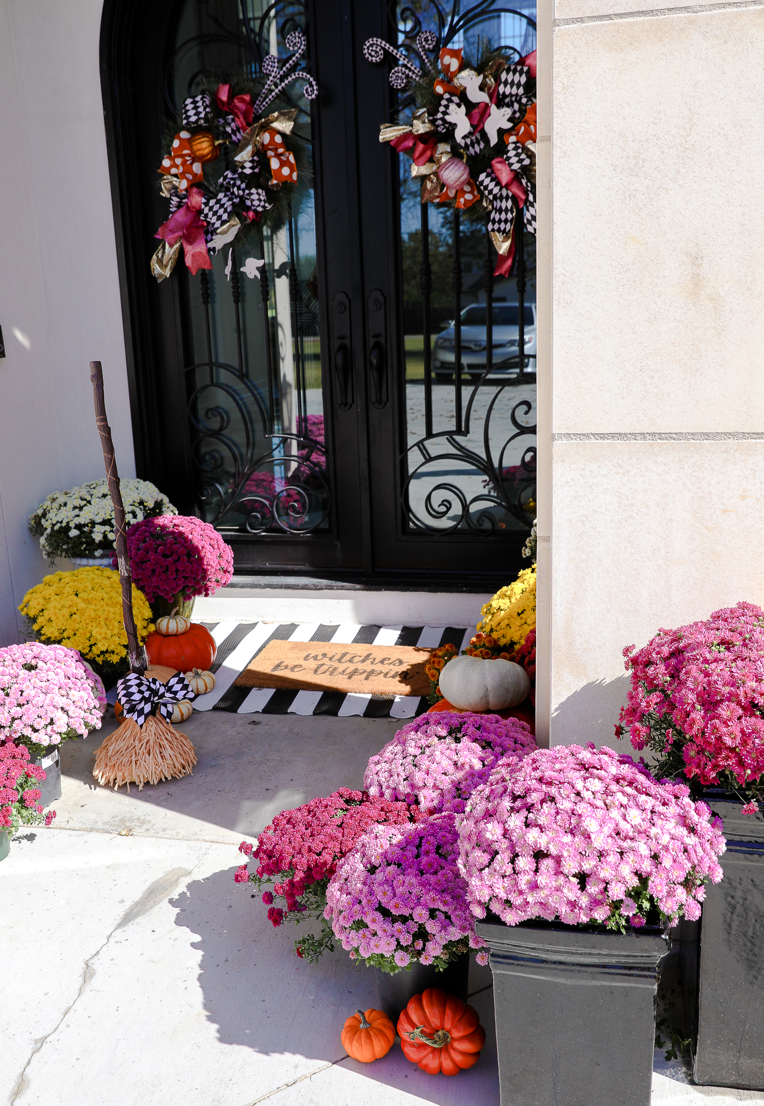 pink mums, front door decor striped rug, pink mums, fall halloween decor, shop hello holidays, emily gemma | Fall & Halloween Home Decor Tour by popular Oklahoma life and style blog, The Sweetest Thing: image of the front entrance to a home decorated with pink mums, pumpkins, a black and white stripe rug, and a welcome mat.
