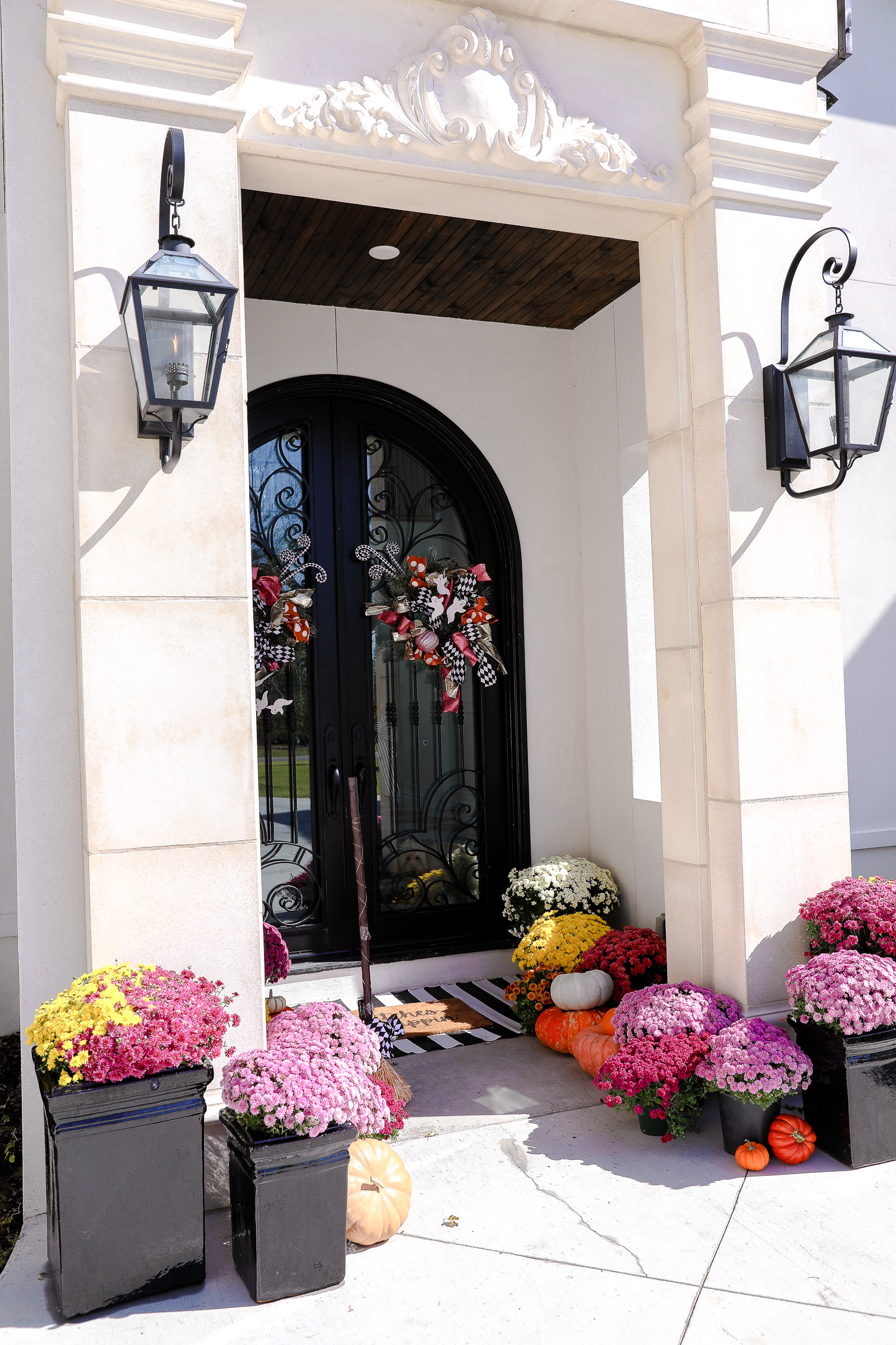 solar gas lights, luxury custom build home, pink mums, front door decor striped rug, pink mums, fall halloween decor, shop hello holidays, emily gemma | Fall & Halloween Home Decor Tour by popular Oklahoma life and style blog, The Sweetest Thing: image of the front entrance to a home decorated with pink mums, pumpkins, a black and white stripe rug, and a welcome mat.