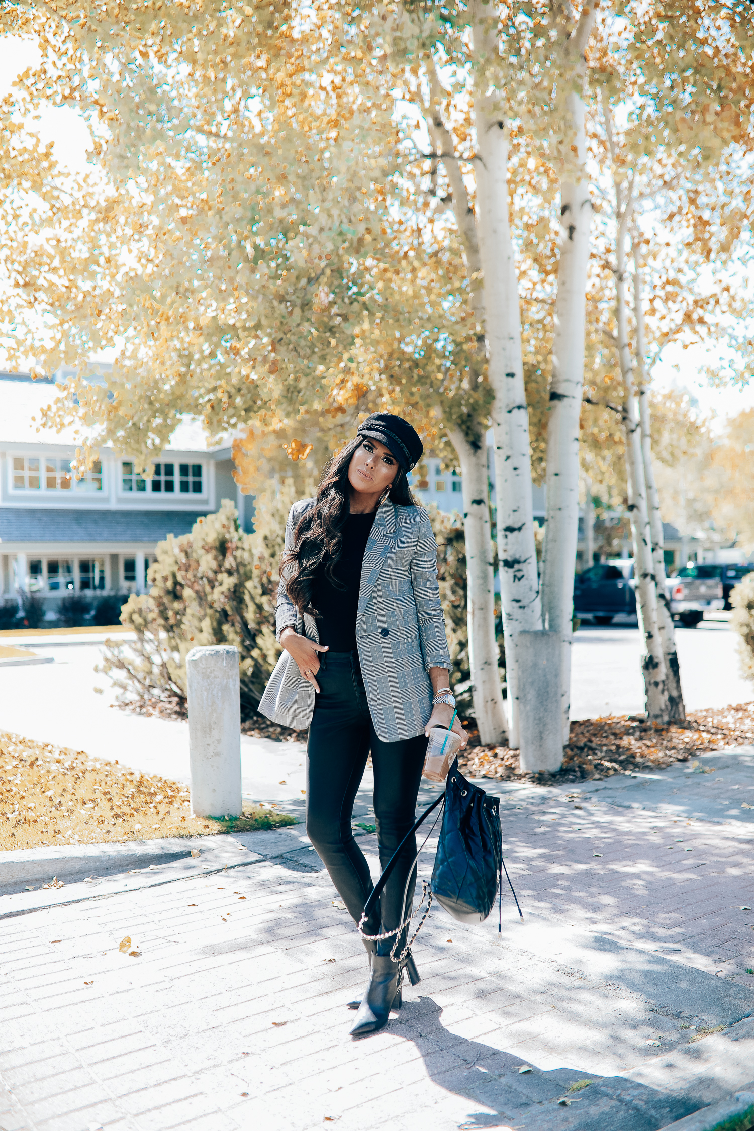 Oversized plaid blazer styled for Fall by top US fashion blog, The Sweetest Thing: image of a woman wearing an Aqua oversized plaid blazer, Splendid long sleeve top, BlankNYC vegan leggings, Marc Fisher booties, Chanel backpack, Baker boy cap, a Rolex watch, Argento Vivo earrings, and Cartier bracelets