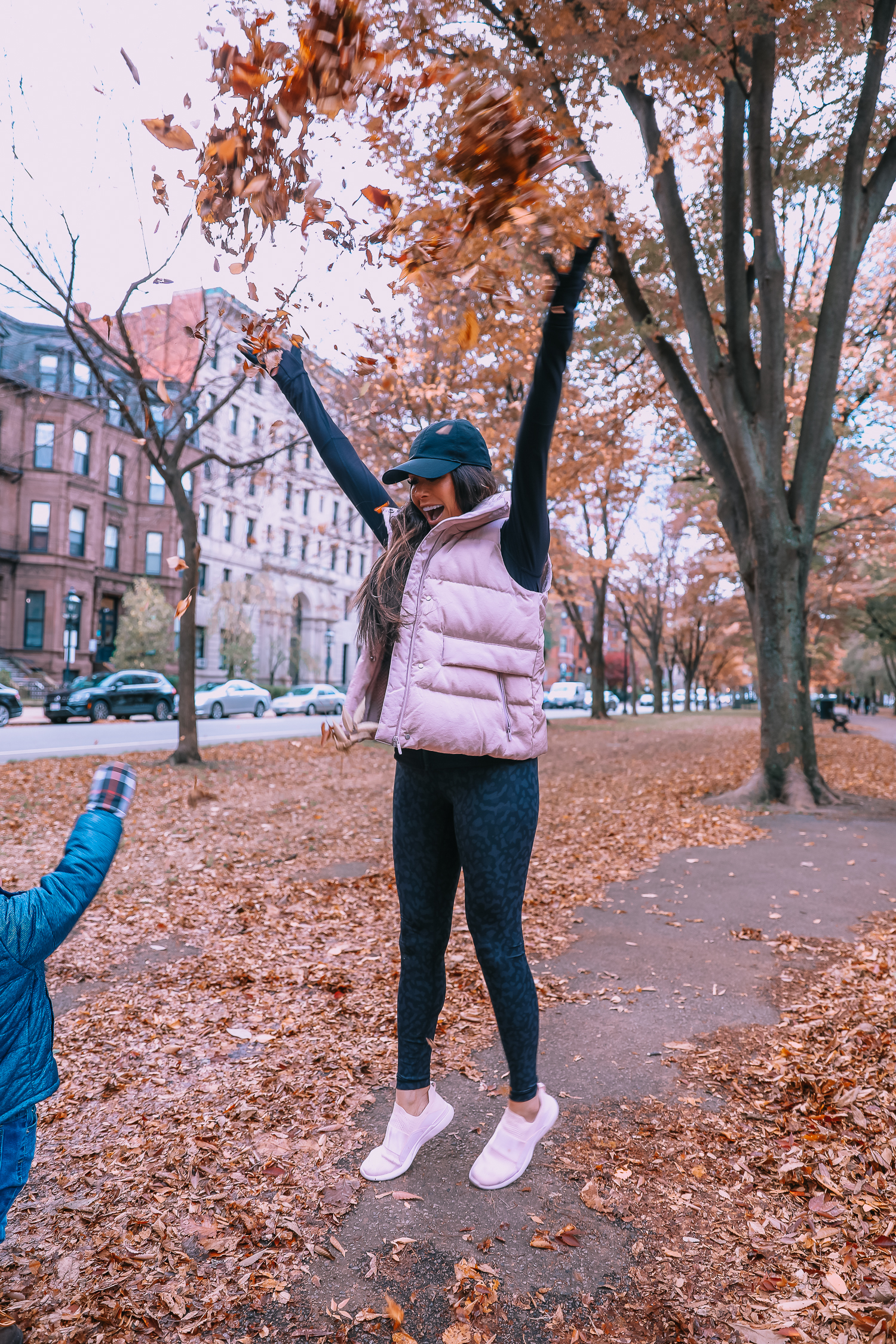 Lululemon Leopard Leggings and Vest Outfit featured by top US fashion blog, The Sweetest Thing: image of a woman wearing Lululemon Leopard Leggings, Lululemon oversized puffer vest, Lululemon black jacket and a Lululemon sports bra.