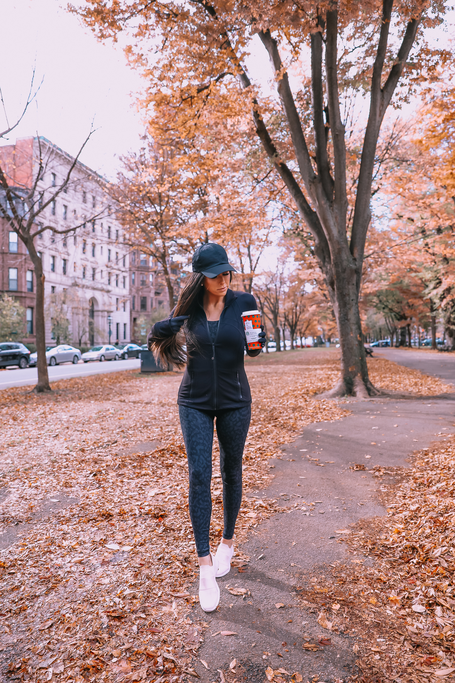 Lulu Lemon Leopard Leggings and Vest Outfit featured by top US fashion blog, The Sweetest Thing: image of a woman wearing Lulu Lemon Leopard Leggings, Lulu Lemon oversized puffer vest, Lulu Lemon black jacket and a Lulu Lemon sports bra.