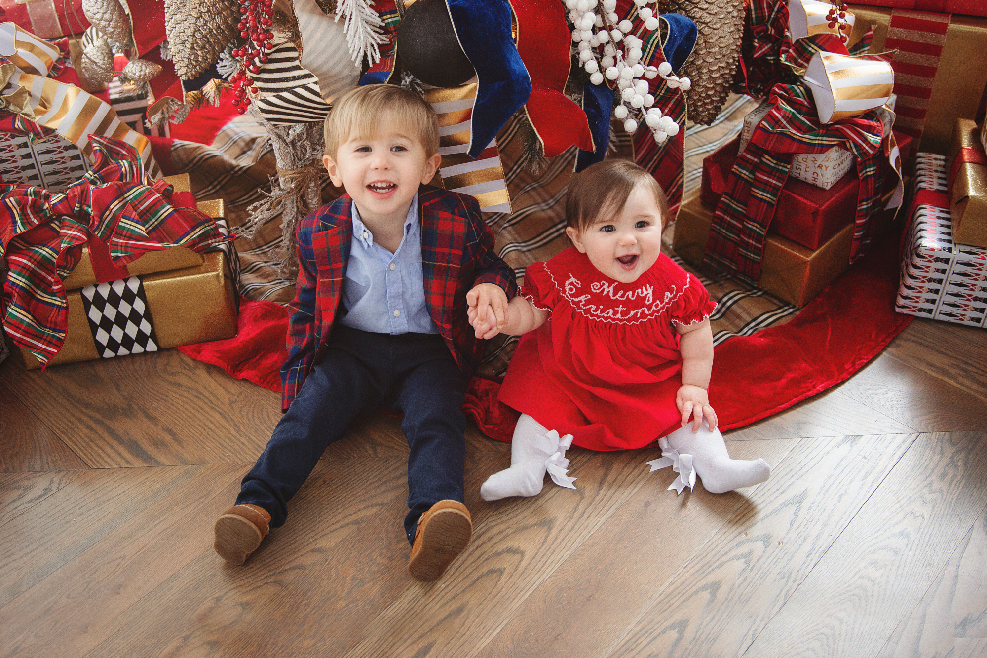 family Christmas card outfit inspiration, smocked Christmas dress baby, baby boy fashion Christmas, pinterest Christmas tree decor, shop hello holidays, Emily Gemma, the sweetest thing blog | Merry Christmas Wishes To You & Yours🎁❤️🎄 [Our Christmas Card 2019] by popular Oklahoma life and style blog, The Sweetest Thing: image a brother and sister sitting in front of their Christmas tree and wearing Smocked Auctions MERRY CHRISTMAS SMOCKED BISHOP RED CORDUROY dress, Zara BASIC SERGED SKINNY JEANS, Zara  LEATHER LOAFERS, Janie and Jack POPLIN SHIRT, Janie and Jack PLAID WOOL BLAZER.