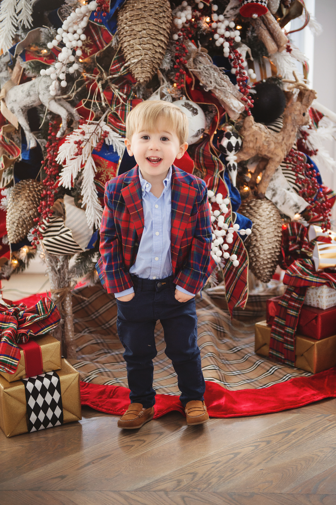 family Christmas card outfit inspiration, smocked Christmas dress baby, baby boy fashion Christmas, pinterest Christmas tree decor, shop hello holidays, Emily Gemma, the sweetest thing blog | Merry Christmas Wishes To You & Yours🎁❤️🎄 [Our Christmas Card 2019] by popular Oklahoma life and style blog, The Sweetest Thing: image of a little boy sitting in front of their Christmas tree and wearing Zara BASIC SERGED SKINNY JEANS, Zara  LEATHER LOAFERS, Janie and Jack POPLIN SHIRT, Janie and Jack PLAID WOOL BLAZER.