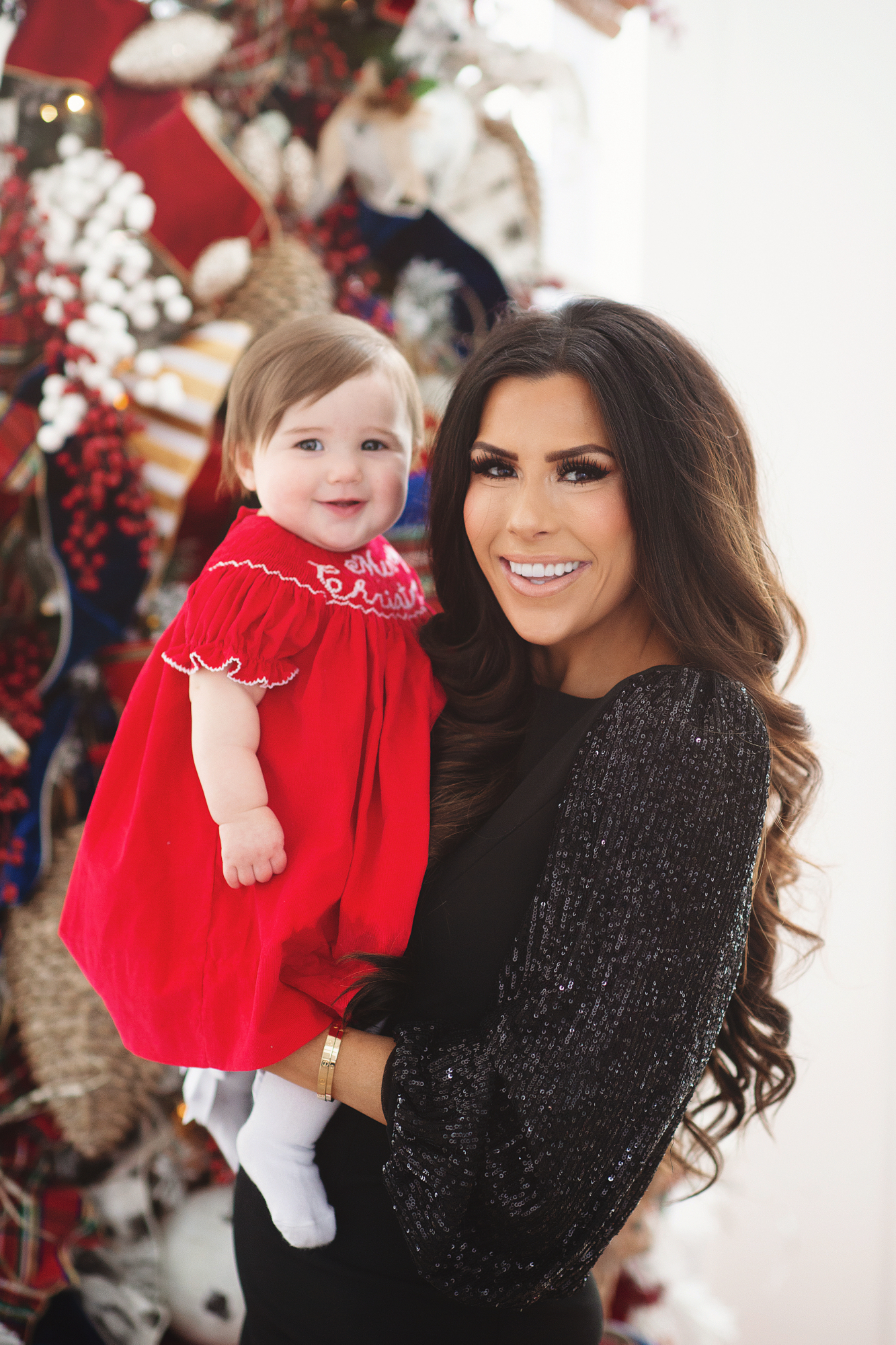 family Christmas card outfit inspiration, smocked Christmas dress baby, baby boy fashion Christmas, pinterest Christmas tree decor, shop hello holidays, Emily Gemma, the sweetest thing blog | Merry Christmas Wishes To You & Yours🎁❤️🎄 [Our Christmas Card 2019] by popular Oklahoma life and style blog, The Sweetest Thing: image a mom holding her baby daughter in front of their Christmas tree and wearing Smocked Auctions MERRY CHRISTMAS SMOCKED BISHOP RED CORDUROY dress, CHRISTIAN LOUBOUTIN So Kate 120 suede pumps, and Nordstrom Eliza J Long Sequin Sleeve Sheath Dress.