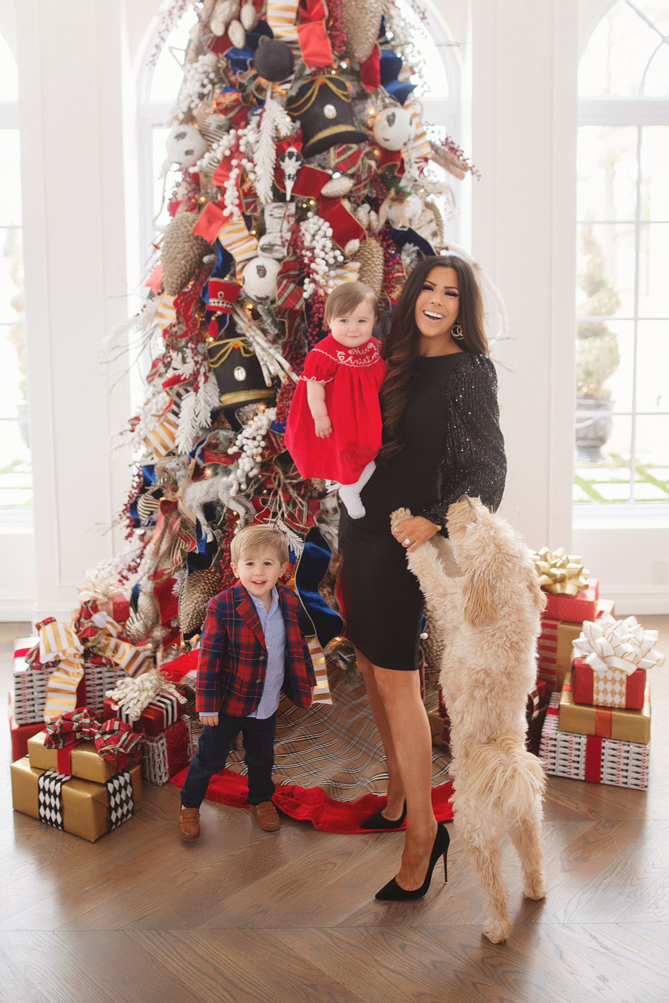 family Christmas card outfit inspiration, smocked Christmas dress baby, baby boy fashion Christmas, pinterest Christmas tree decor, shop hello holidays, Emily Gemma, the sweetest thing blog | Merry Christmas Wishes To You & Yours🎁❤️🎄 [Our Christmas Card 2019] by popular Oklahoma life and style blog, The Sweetest Thing: image a family standing in front of their Christmas tree and wearing Smocked Auctions MERRY CHRISTMAS SMOCKED BISHOP RED CORDUROY dress, Zara BASIC SERGED SKINNY JEANS, Zara  LEATHER LOAFERS, Janie and Jack POPLIN SHIRT, Janie and Jack PLAID WOOL BLAZER, CHRISTIAN LOUBOUTIN So Kate 120 suede pumps, and Nordstrom Eliza J Long Sequin Sleeve Sheath Dress.