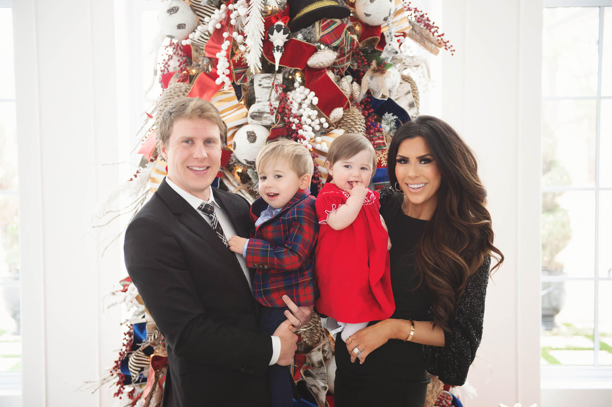 family Christmas card outfit inspiration, smocked Christmas dress baby, baby boy fashion Christmas, pinterest Christmas tree decor, shop hello holidays, Emily Gemma, the sweetest thing blog | Merry Christmas Wishes To You & Yours🎁❤️🎄 [Our Christmas Card 2019] by popular Oklahoma life and style blog, The Sweetest Thing: image a family standing in front of their Christmas tree and wearing Smocked Auctions MERRY CHRISTMAS SMOCKED BISHOP RED CORDUROY dress, Zara BASIC SERGED SKINNY JEANS, Zara  LEATHER LOAFERS, Janie and Jack POPLIN SHIRT, Janie and Jack PLAID WOOL BLAZER, Nordstrom Burberry men's tie, Nordstrom Boss Huge/Genius Trim Fit Solid Wool Suit, CHRISTIAN LOUBOUTIN So Kate 120 suede pumps, and Nordstrom Eliza J Long Sequin Sleeve Sheath Dress.