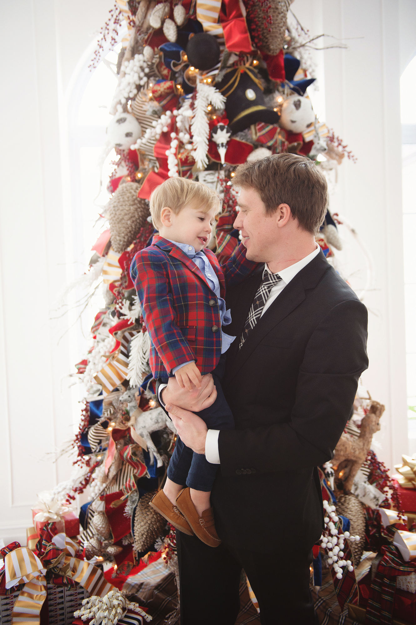 family Christmas card outfit inspiration, smocked Christmas dress baby, baby boy fashion Christmas, pinterest Christmas tree decor, shop hello holidays, Emily Gemma, the sweetest thing blog | Merry Christmas Wishes To You & Yours🎁❤️🎄 [Our Christmas Card 2019] by popular Oklahoma life and style blog, The Sweetest Thing: image a dad and son standing in front of their Christmas tree and wearing a Zara BASIC SERGED SKINNY JEANS, Zara  LEATHER LOAFERS, Janie and Jack POPLIN SHIRT, Janie and Jack PLAID WOOL BLAZER, Nordstrom Burberry men's tie, Nordstrom Boss Huge/Genius Trim Fit Solid Wool Suit.