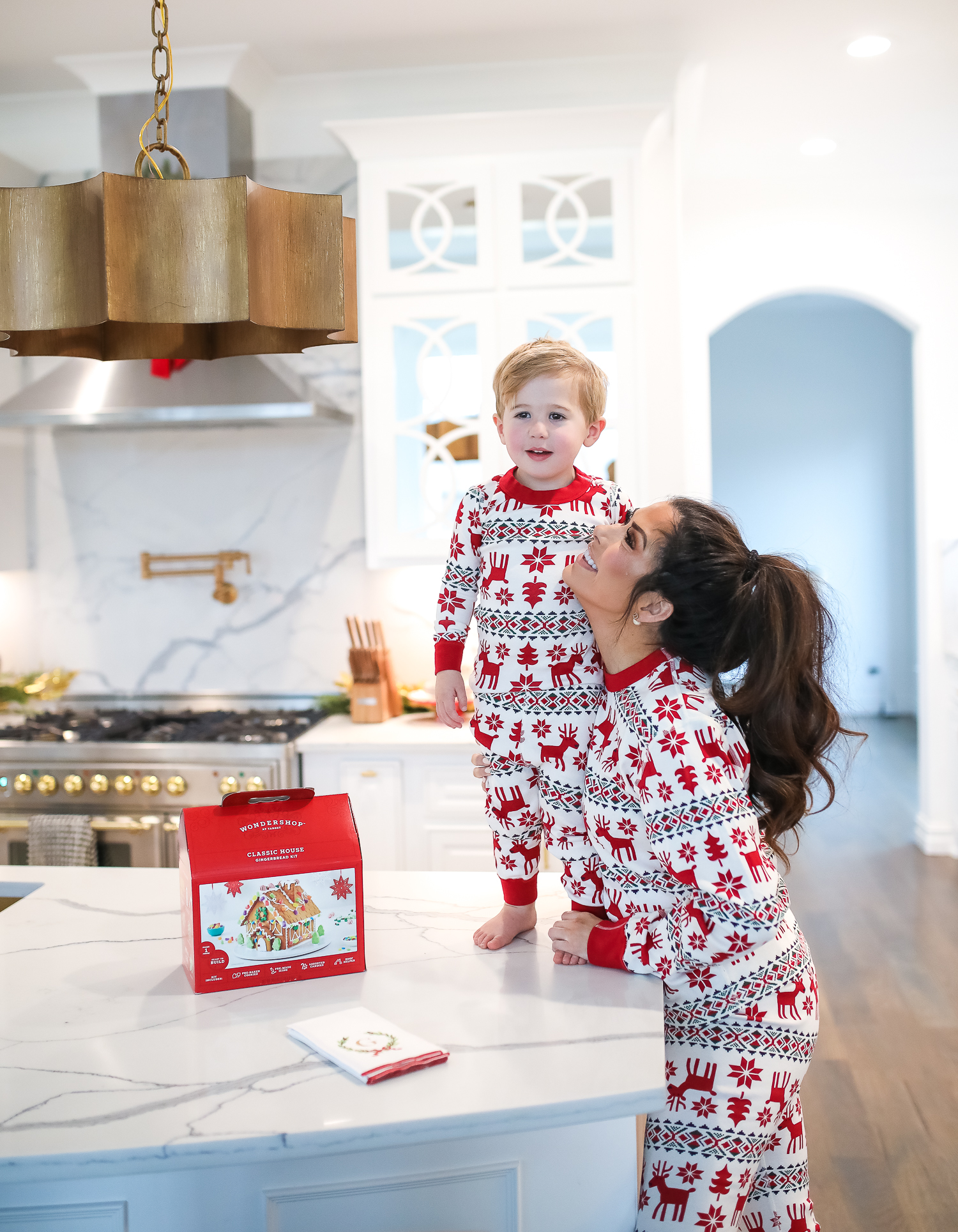 Hanna Anderson pjs christmas, family matching christmas pajamas, christmas decor pajamas 2019 pinterest, babies christmas pajamas matching, the sweetest thing blog-5 | Coco & Crew In Matching Hanna Andersson Christmas Pajamas by popular Oklahoma life and style blog, The Sweetest Thing: image of a family decorating gingerbread houses and wearing Hanna Andersson Long John Pajamas In Organic Cotton, Hanna Andersson Adult Long John Pant In Organic Cotton, Hanna Andersson Women's Long John Top In Organic Cotton, Hanna Andersson Adult Long John Top In Organic Cotton, and Hanna Andersson Adult Long John Pant In Organic Cotton.