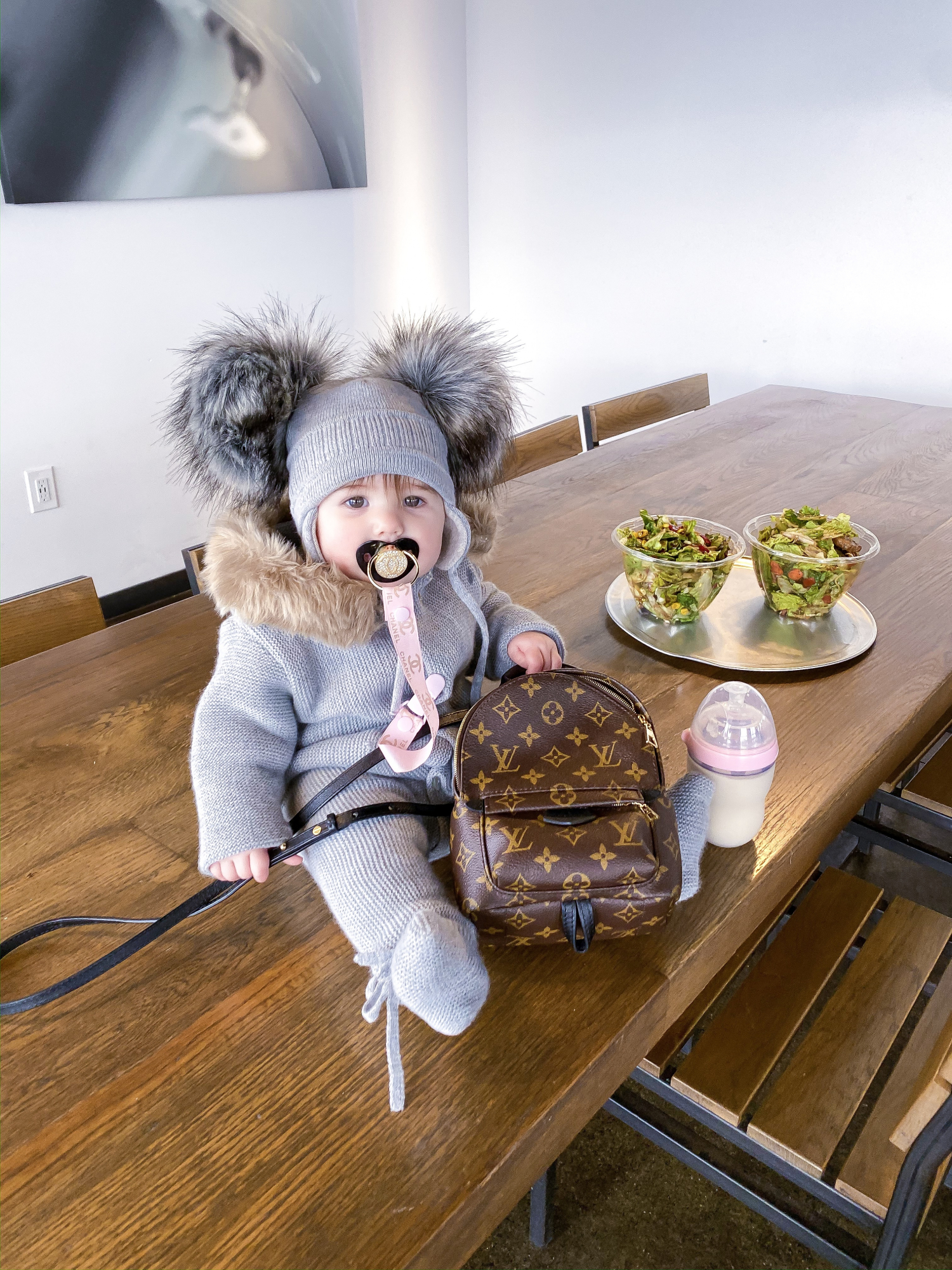 baby girl fashion pinterest, louis vuitton palm springs backpack | A YEAR IN REVIEW : MASSIVE 2019 INSTAGRAM RECAP by popular Oklahoma life and style blog, The Sweetest Thing: image of a baby sitting on a table next to some salad bowls and wearing a grey double pom-pom hat and holding a Louis Vuitton mini backpack.