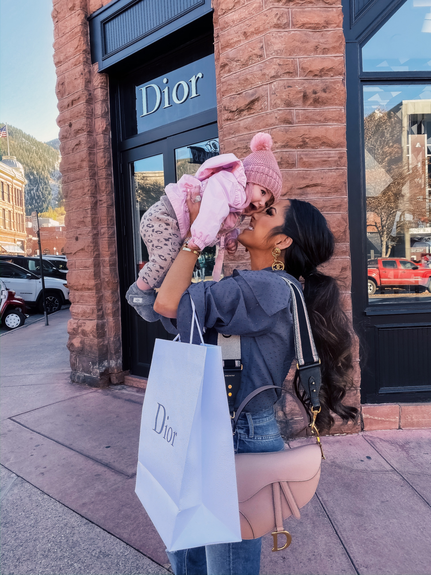baby girl fashionista, dior in aspen, dior nude saddle bag, emily gemma | A YEAR IN REVIEW : MASSIVE 2019 INSTAGRAM RECAP by popular Oklahoma life and style blog, The Sweetest Thing: image of a woman holding her baby outside a Dior store in Aspen, Colorado and wearing Chanel earrings, Nordstrom Tie Neck Dobby Blouse TOPSHOP, and Nordstrom The Tripper High Waist Crop Bootcut Jeans MOTHER.