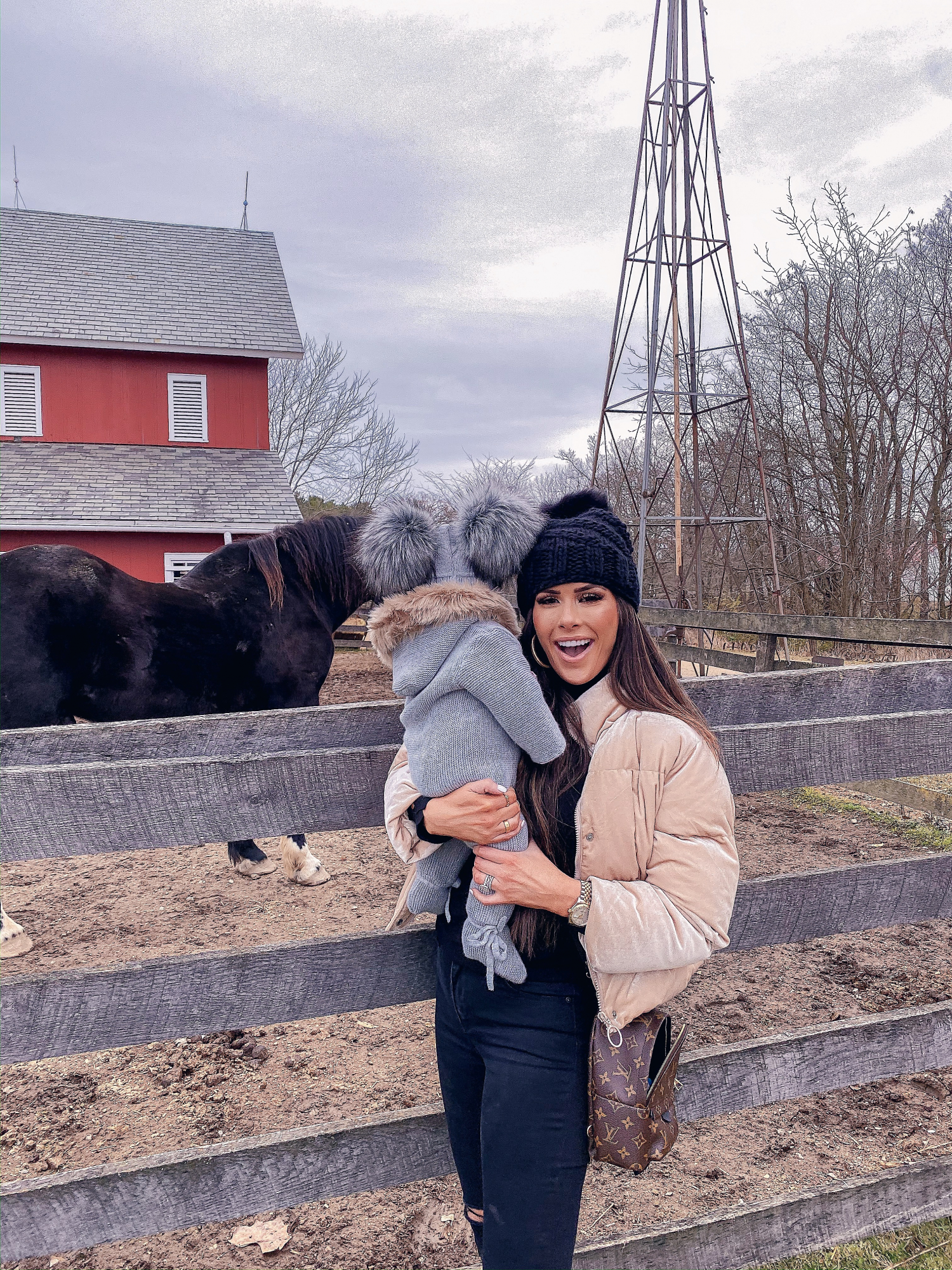 baby girl fashionista, double pom pom beanie | A YEAR IN REVIEW : MASSIVE 2019 INSTAGRAM RECAP by popular Oklahoma life and style blog, The Sweetest Thing: image of a mom holding her baby next to a black horse and wearing a Nordstrom Joan of Arctic II Lux Wedge Genuine Shearling Bootie SOREL, Louis Vuitton mini backpack, Nordstrom Mile High Ripped Super Skinny Jeans LEVI'S®, and BUDDYLOVE NICKS PUFFY ZIPPER CLOSURE JACKET - PEARL.