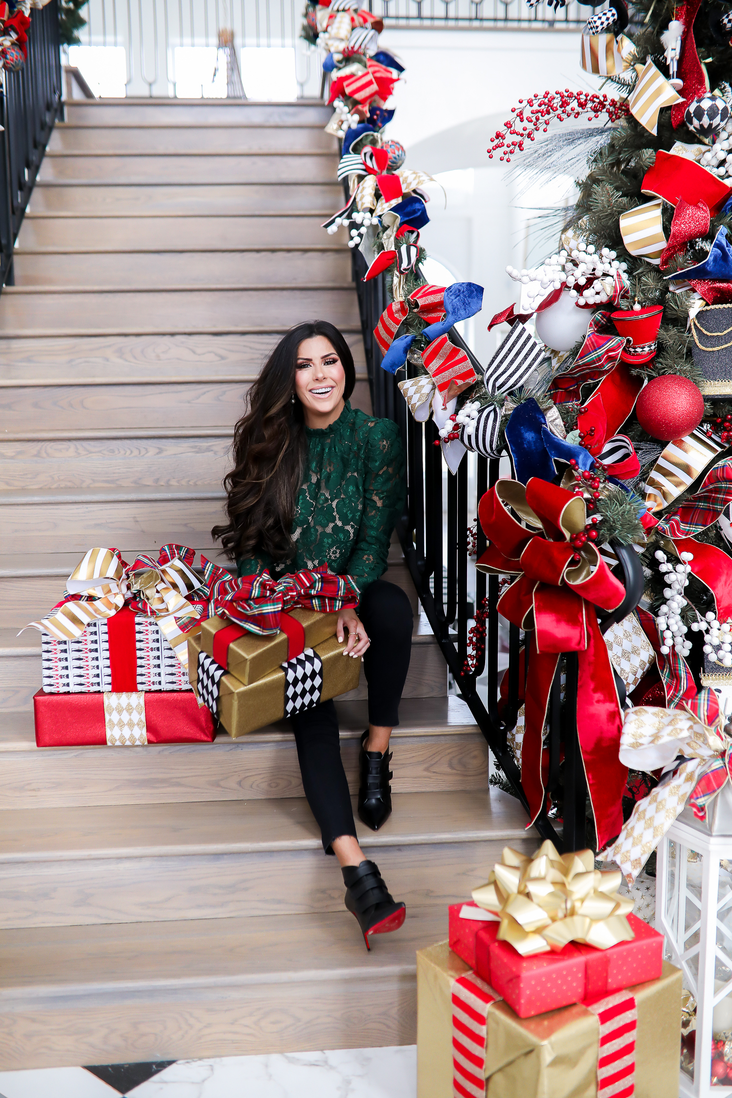 christmas tree inspiration, pinterest christmas tree inspiration 2019, gift ideas gift guide 2019, wayf lace top, chanel black gold belt, best christmas tree home decor, black loubtouin booties-2 | FAVORITE GIFT IDEAS FOR HER + MEGA GIVEAWAY [+Louis Vuitton Wallet] by popular Oklahoma life and style blog, The Sweetest Thing: image of a woman sitting on a staircase next to a pile of presents.