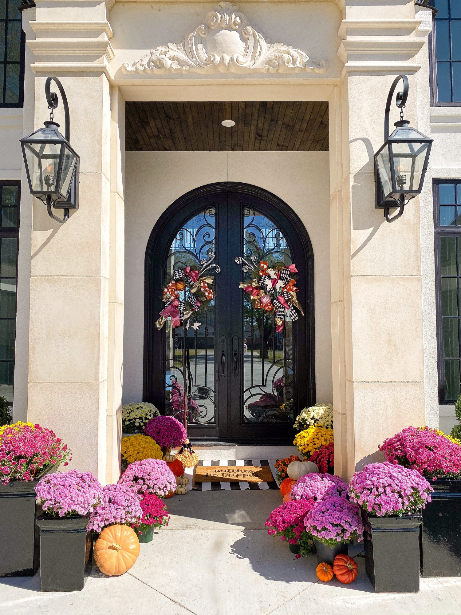 fall front door decor mums pinterest, emily gemma, shop hello holidays | A YEAR IN REVIEW : MASSIVE 2019 INSTAGRAM RECAP by popular Oklahoma life and style blog, The Sweetest Thing: image of a front porch decorated with various colored potted mums and pumpkins.