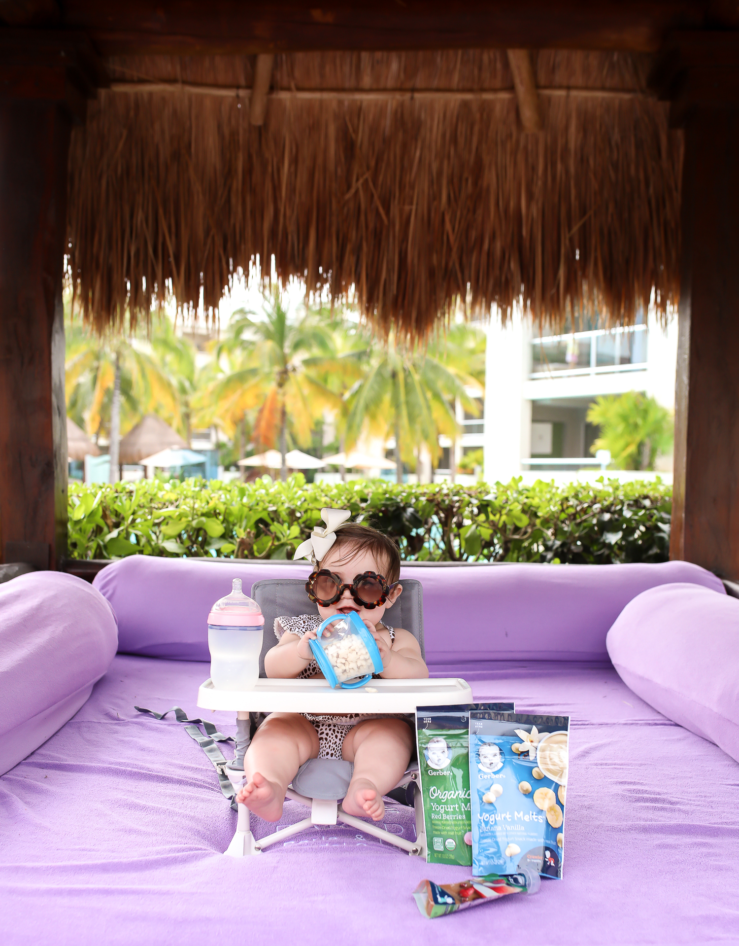 Christmas In Cancun🌟🎄🎁 [+ A Few Baby Travel Must-Haves] by popular Oklahoma travel blog, The Sweetest Thing: image of a baby in Cancun, Mexico sitting in a Walmart hiccapop Omniboost Travel Booster Seat with Tray for Baby holding a Walmart Munchkin Snack Catcher Snack Cup with Gerber Puff cereal snack inside, with a bottle resting on her high chair tray and some Gerber Organic Yogurt melts next to her high chair.