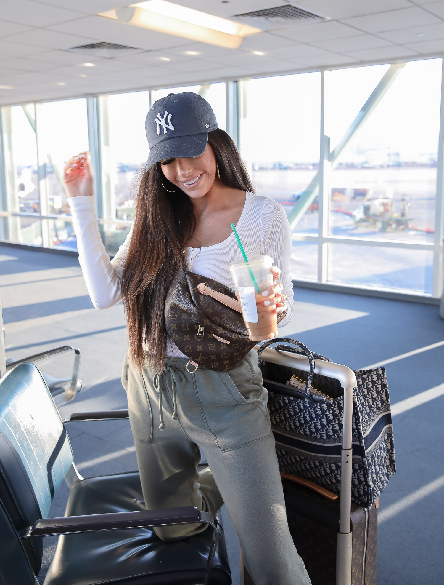 airport outfit idea, cute airport fashion outfit, dior sneakers womens 2020, pinterest airport fashion, horizon louis vuitton carryon, dior oblique tote, emily gemma-2 | Airport Style by popular US life and style blog, The Sweetest Thing: image of a woman in an airport wearing a Abercrombie Long-Sleeve Cozy Henley, Abercrombie High Rise Joggers, Dior WALK'N'DIOR SNEAKER IN OBLIQUE EMBROIDERED CANVAS, Nordstrom 21-Inch Rolling Spinner Suitcase, Nordstrom Demonbreun Hoop Earrings UNCOMMON JAMES BY KRISTIN CAVALLARI, Nordstrom Lip Cheat Lip Liner CHARLOTTE TILBURY, Nordstrom Hot Lips Lipstick CHARLOTTE TILBURY, Nordstrom Gloss Luxe Moisturizing Lipgloss TOM FORD, and Urban Outfitters MLB Baseball Hat.