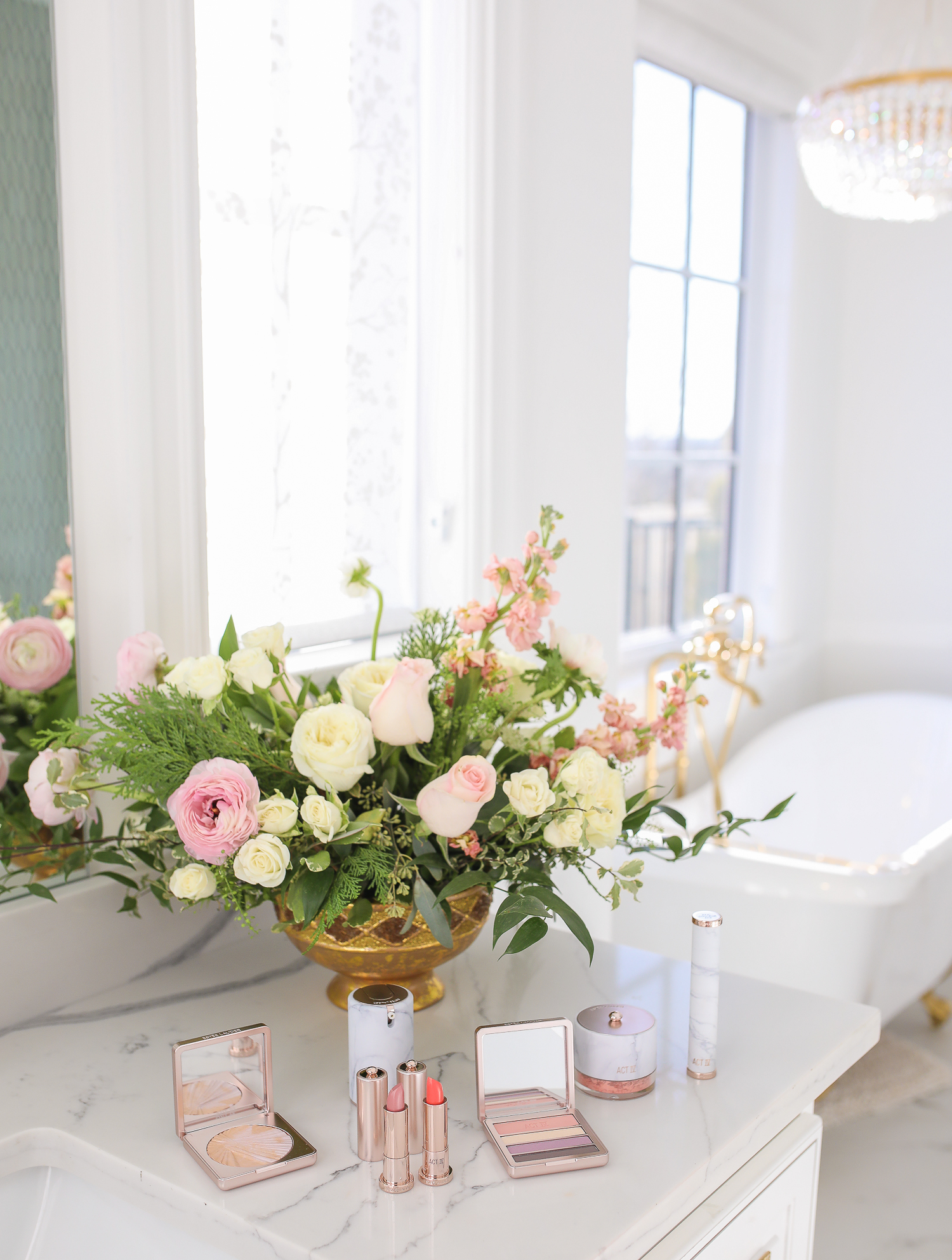 Estee Lauder Makeup by popular US beauty blog, The Sweetest Thing: image of various Estee Lauder Act IV makeup products on a bathroom counter next to a vase of flowers.