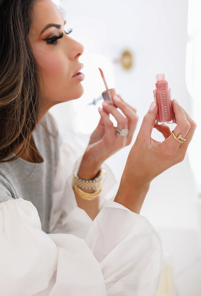 Sephora Haul by popular US beauty blog, The Sweetest Thing: image of a woman applying Fenty beauty lipgloss.