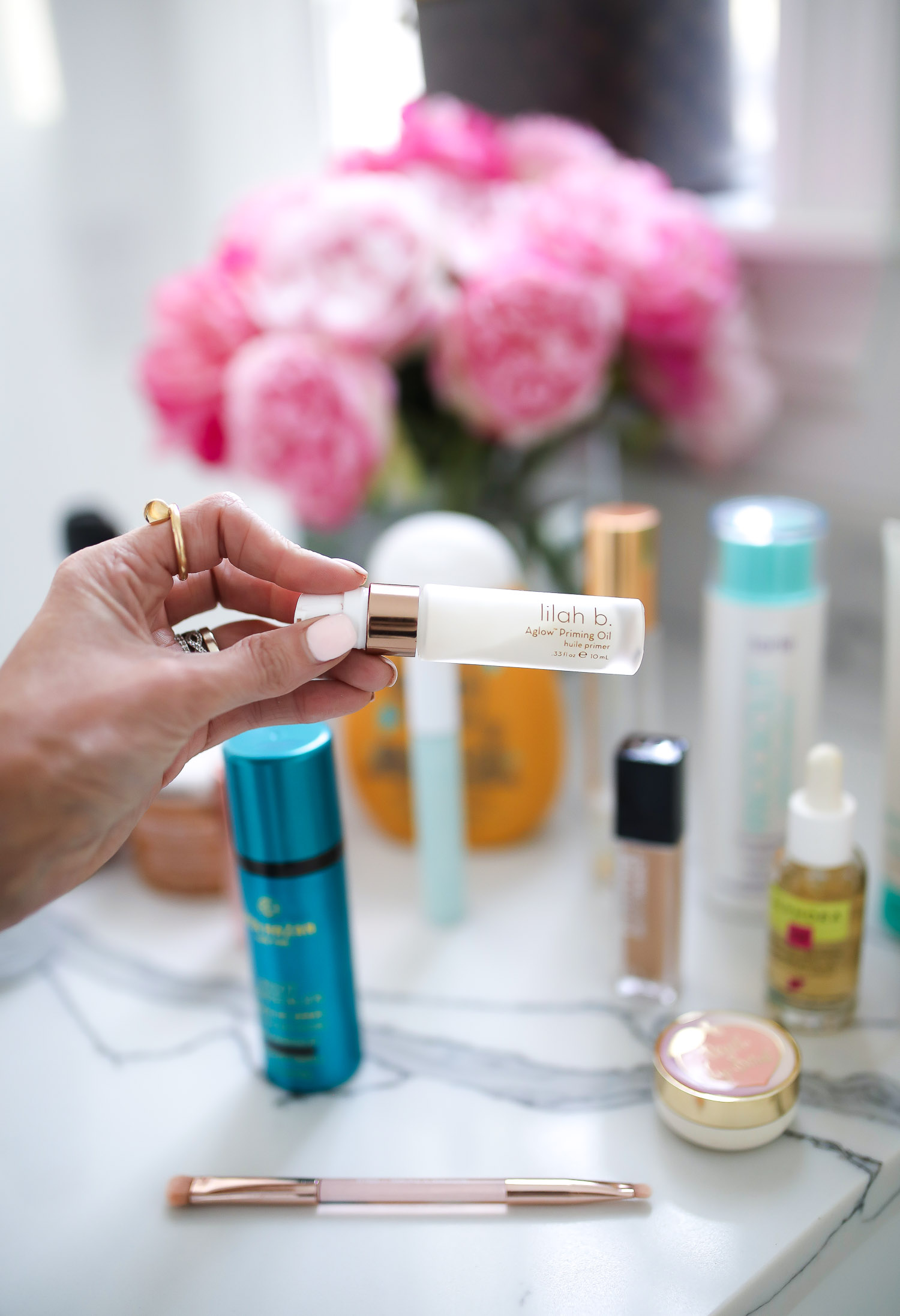 Sephora Favorites by popular US beauty blog, The Sweetest Thing: image of a woman holding Lilah B priming oil in her hand.