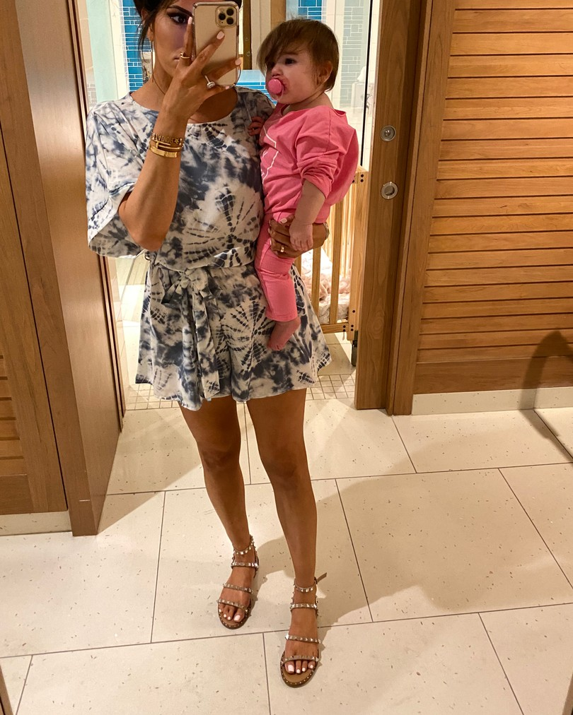 Instagram Fashion by popular US fashion blog, The Sweetest Thing: image of a woman holdign her baby and wearing a Red Dress Cool Touch Blue Tie Dye Print Romper and Steve Madden TRAVEL TAN sandals.