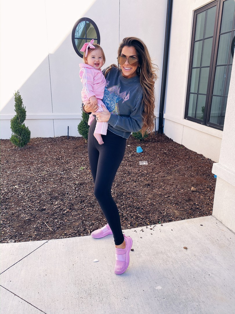 Instagram Recap by popular US lifestyle blog, The Sweetest Thing: image of Emily Gemma holding her daughter and wearing a Nordstrom Def Leppard Crop Sweatshirt VINYL ICONS, Nordstrom Live In High Waist Pocket 7/8 Leggings ZELLA, APL Women's TechLoom Bliss, Nordstrom High Key 65mm Oversize Rimless Aviator Sunglasses QUAY AUSTRALIA, Amazon adidas Baby Girls' Li'l Sport Tricot Pant & Jacket Active Clothing Set, and Amazon Ceelgon Big Hair Bow.