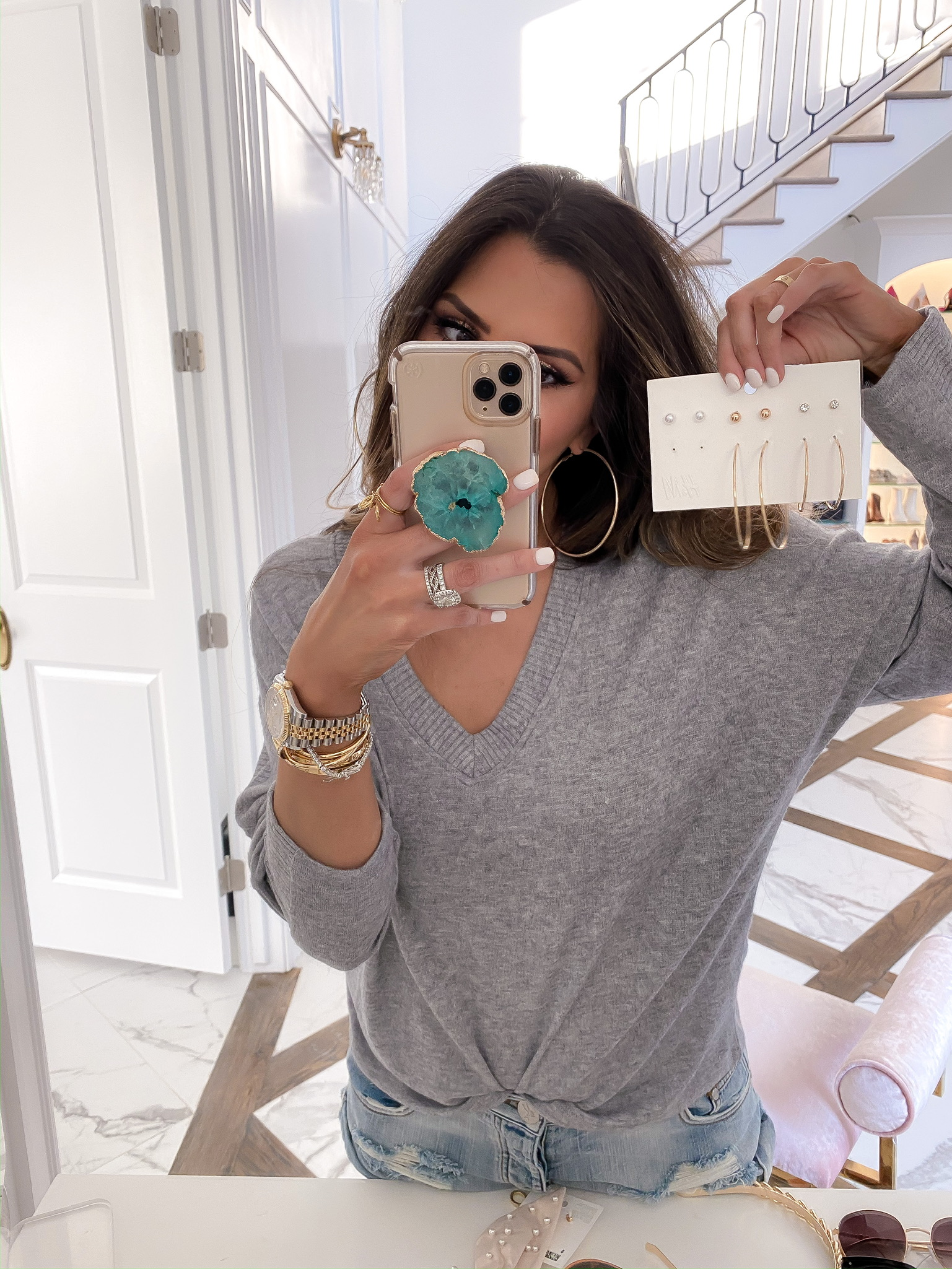 Blogging Newsletter by popular US life and style blog, The Sweetest Thing: image of a woman holding some H&M 6-pack Earrings and Studs.