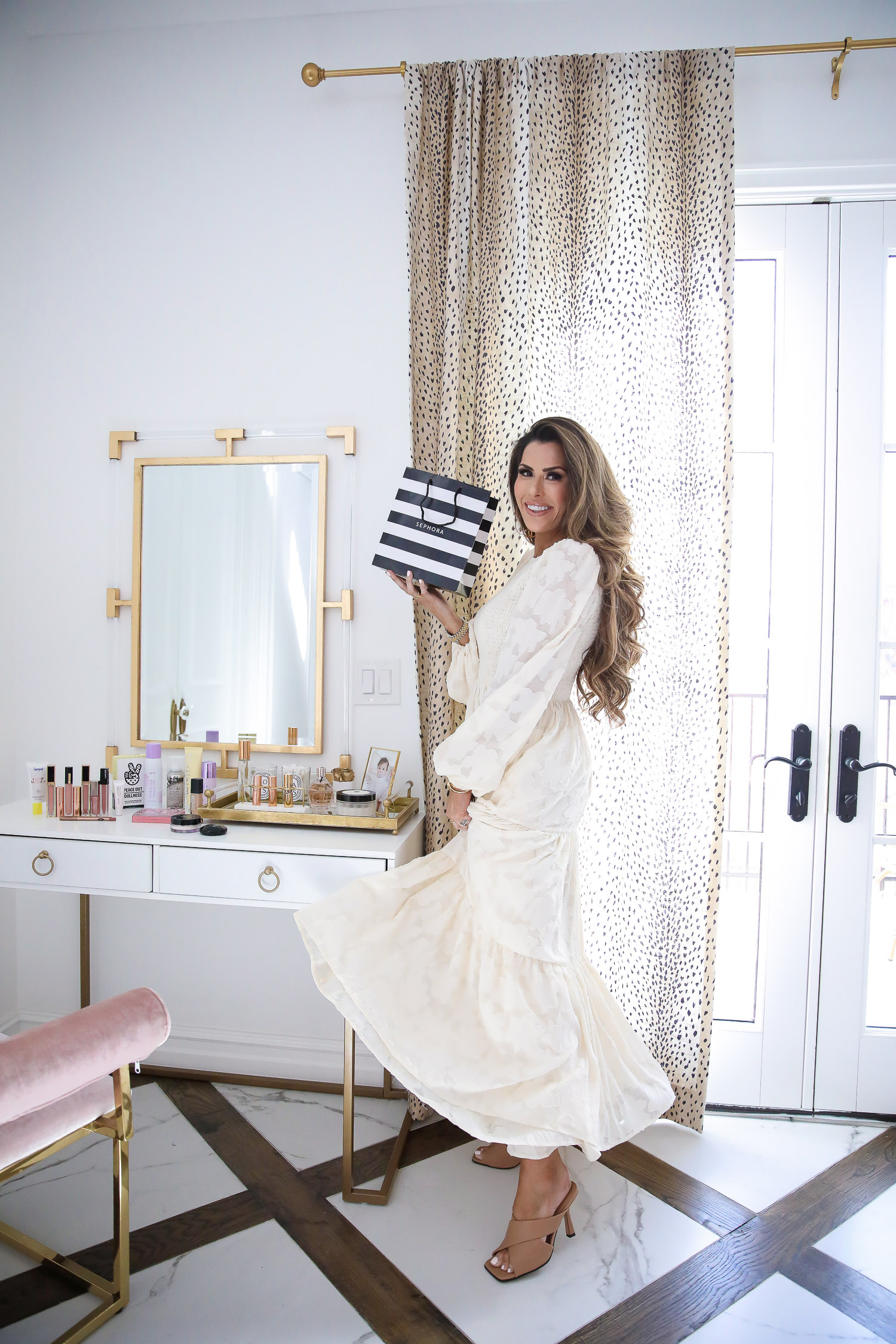 Sephora Haul spring 2020, beauty bloggers, Tatcha Liquid Silk Canvas review, lawless makeup review, emily gemma | Sephora Favorites by popular US beauty blog, The Sweetest Thing: image of a woman wearing cream maxi dress and holding a Sephora makeup bag while standing next to her vanity.