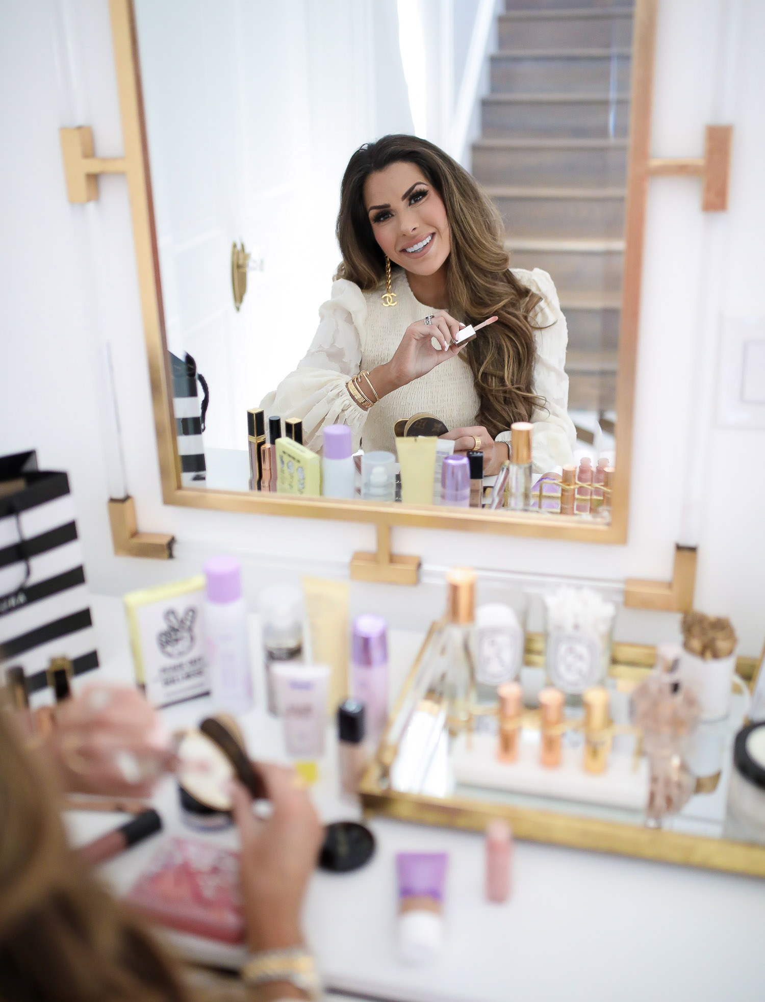 Sephora Haul spring 2020, beauty bloggers, Tatcha Liquid Silk Canvas review, lawless makeup review, emily gemma | Sephora Favorites by popular US beauty blog, The Sweetest Thing: image of a woman applying lipgloss in her vanity mirror.