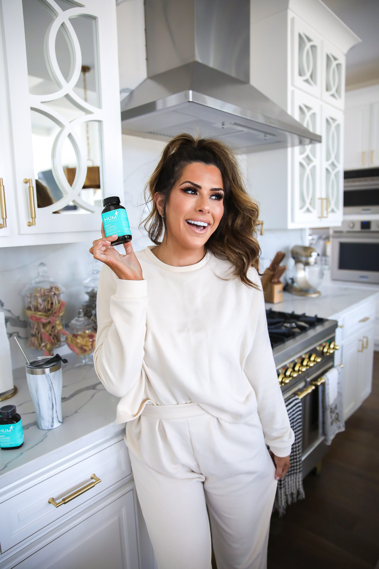 hum nutrition daily cleanse supplements, skin clearing vitamins, green algae vitamins, emily gemma skincare routine | Hum Daily Cleanse by popular US lifestyle blog, The Sweetest Thing: image of a woman wearing a cream colored lounge set and holding a bottle Hum Daily Cleanse supplements.