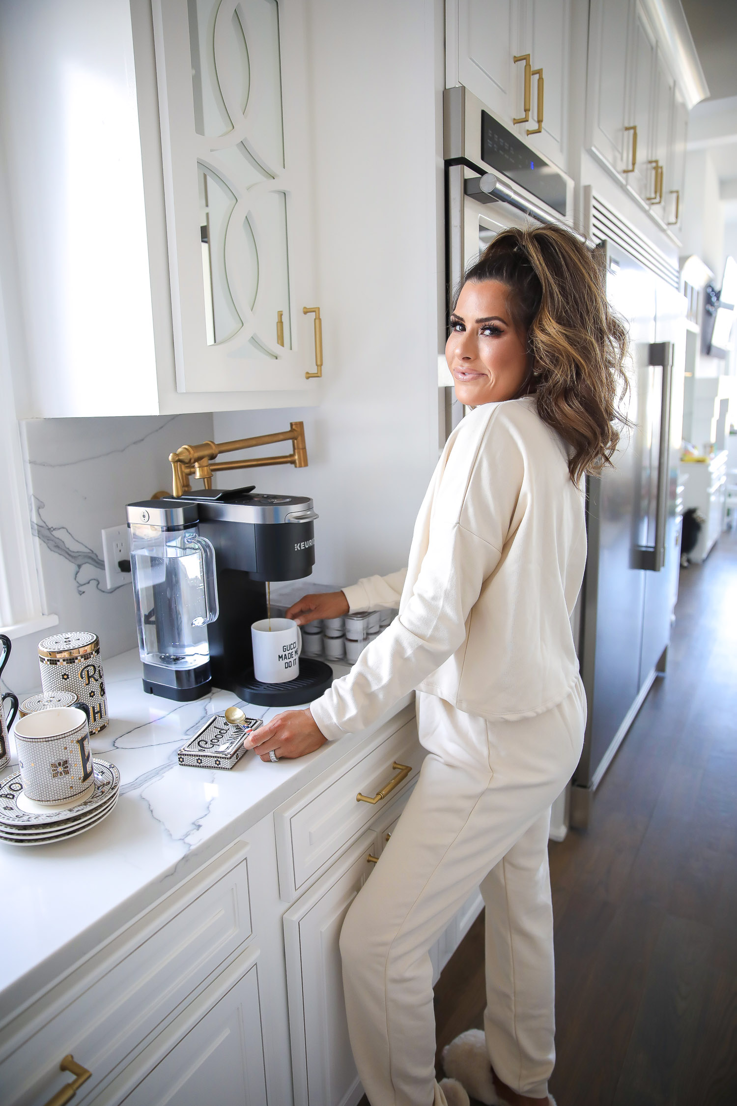 hum nutrition daily cleanse supplements, skin clearing vitamins, green algae vitamins, emily gemma skincare routine | Hum Daily Cleanse by popular US lifestyle blog, The Sweetest Thing: image of a woman wearing a cream colored lounge set and getting herself a cup of coffee from her coffee maker.
