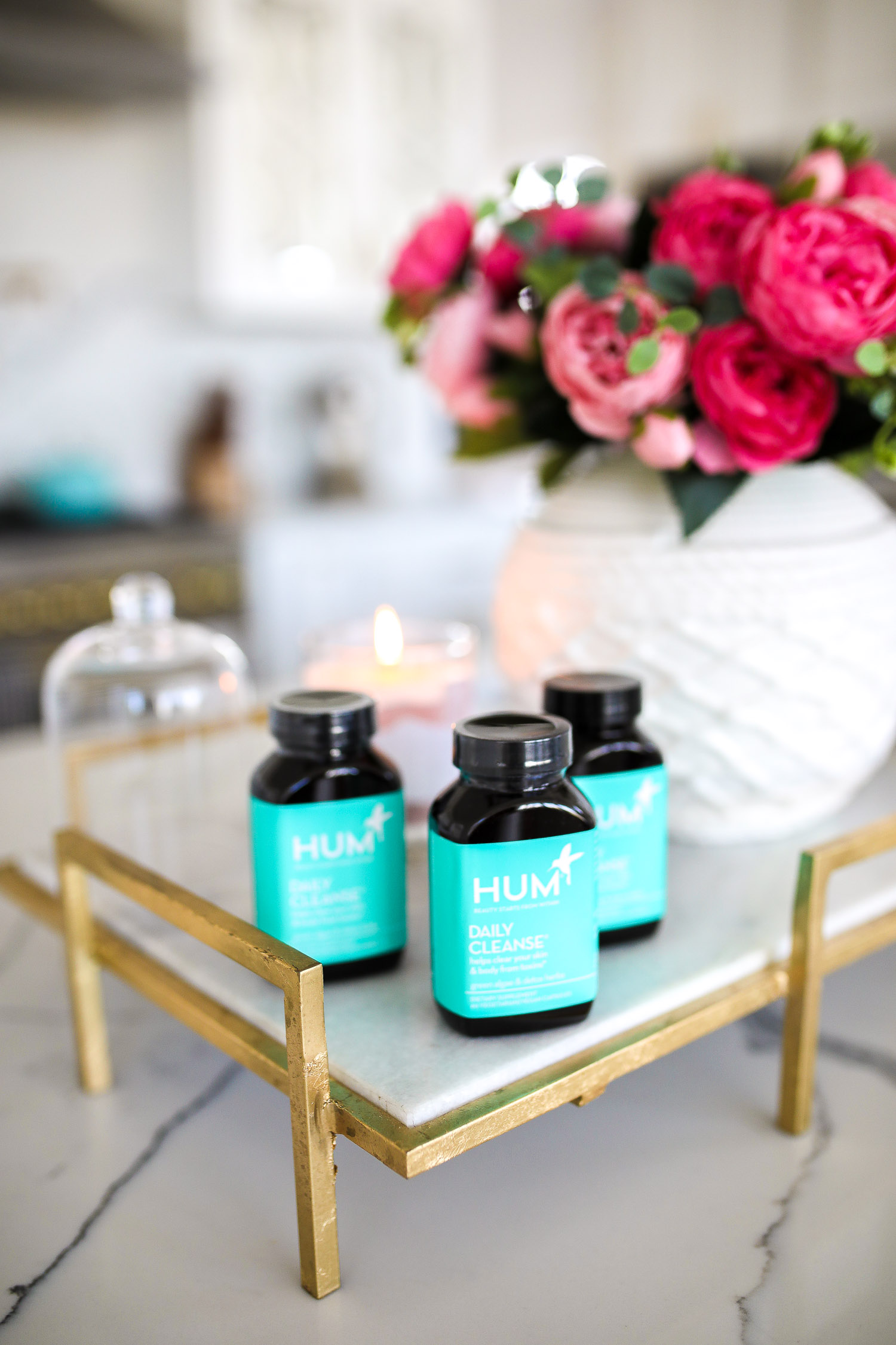 hum nutrition daily cleanse supplements, skin clearing vitamins, green algae vitamins, emily gemma skincare routine | Hum Daily Cleanse by popular US lifestyle blog, The Sweetest Thing: image of 3 bottle of Hum Daily Cleanse supplement bottles next to a white ceramic vase with pink roses in it.