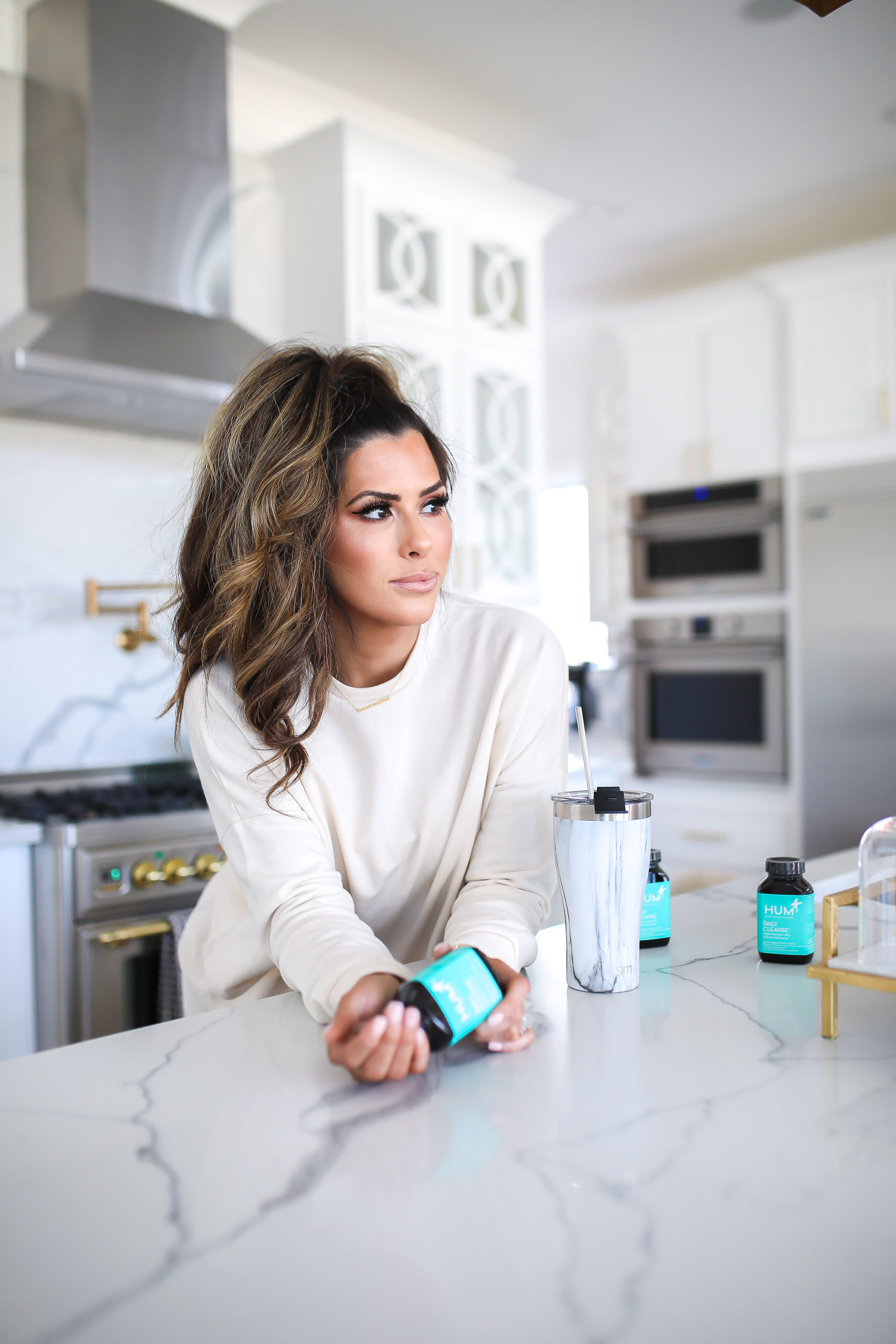 hum nutrition daily cleanse supplements, skin clearing vitamins, green algae vitamins, emily gemma skincare routine | Hum Daily Cleanse by popular US lifestyle blog, The Sweetest Thing: image of a woman wearing a cream colored lounge set and pouring some Hum Daily Cleanse supplements into her hand.