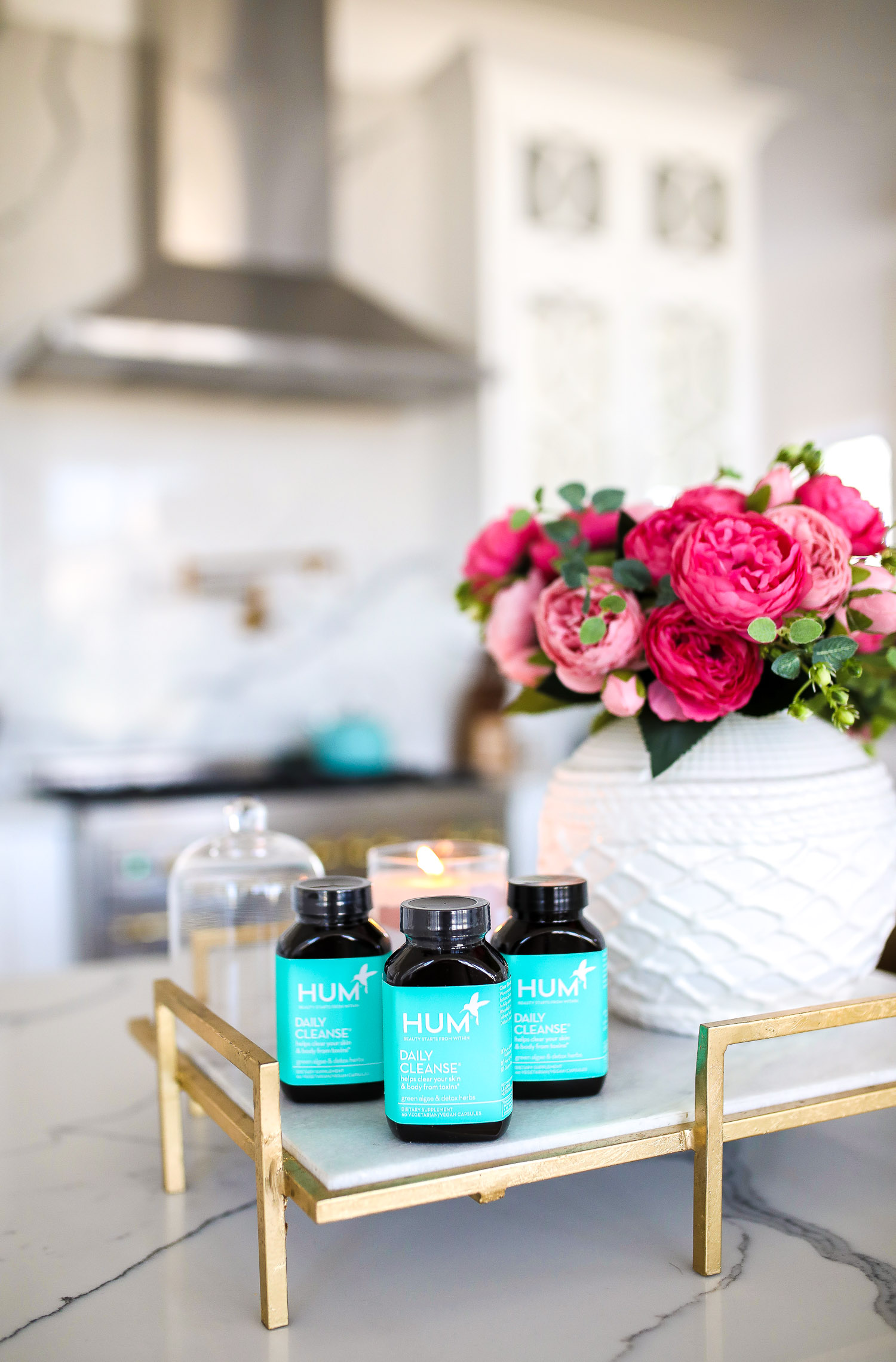 hum nutrition daily cleanse supplements, skin clearing vitamins, green algae vitamins, emily gemma skincare routine | Hum Daily Cleanse by popular US lifestyle blog, The Sweetest Thing: image of three bottles of Hum Daily Cleanse supplements next to a white ceramic vase filled with pink roses.