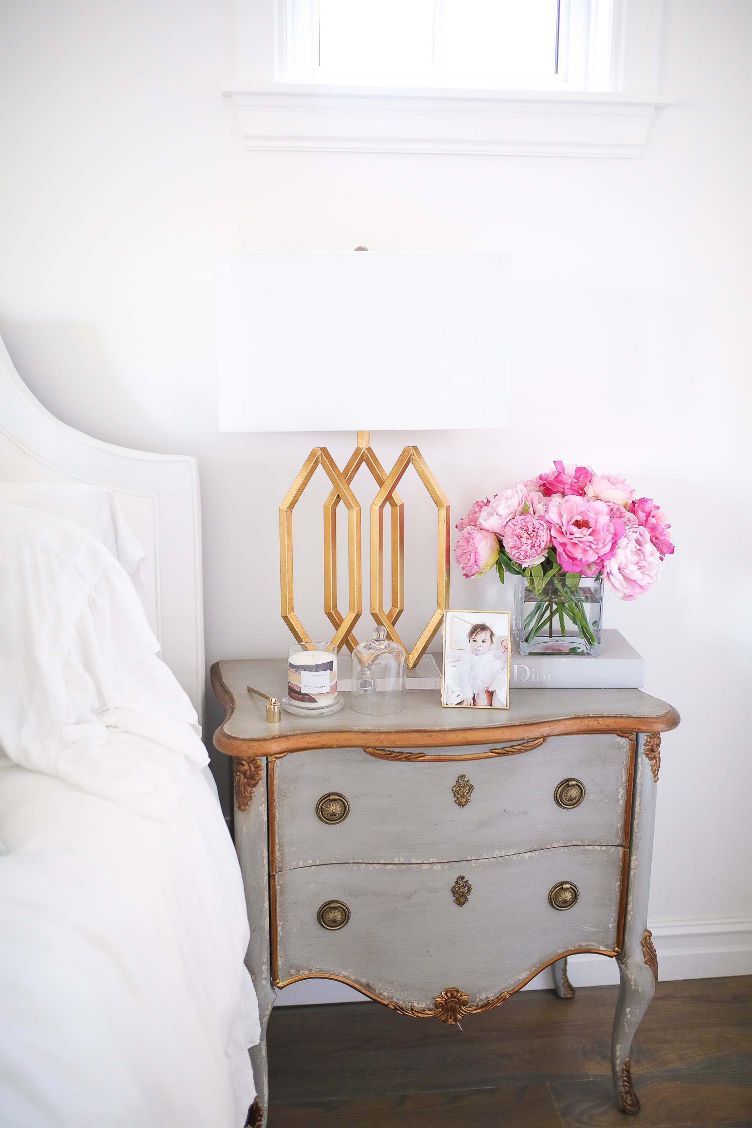 Barefoot dreams blankets, spring gift ideas 2020, commando butter bra reivew, see by chloe wedges, nordstrom must haves spring 2020, emily gemma | Things That Make Me Happy by popular US lifestyle blog, The Sweetest Thing: image of a grey night stand with a gold lamp, gold picture frame, candle, and vase of pink flowers on top.