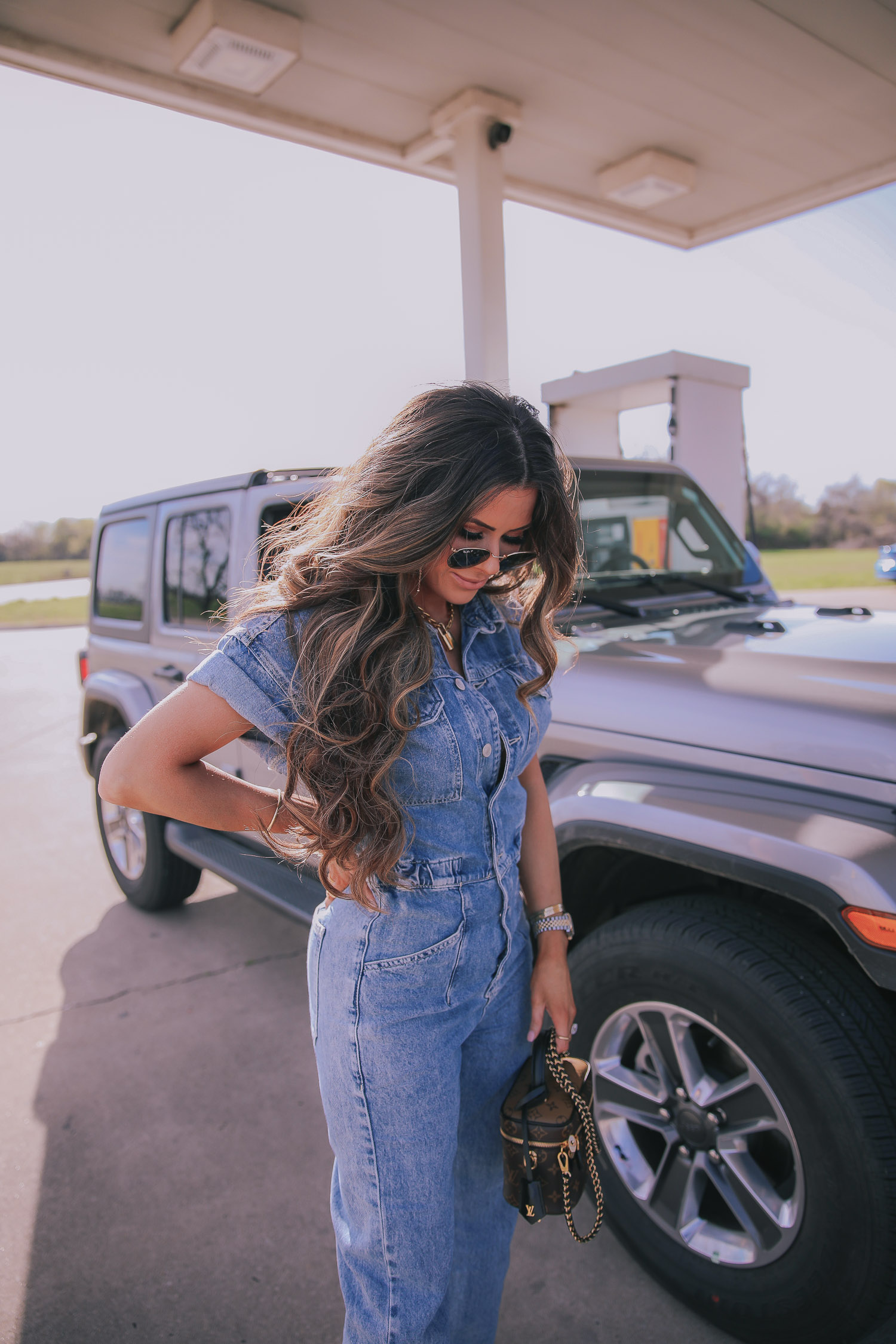 denim jumpsuit, free people denim jumpsuit coverall, emily ann gemma, spring fashion 2020, pinterest spring summer fashion 2020 | Denim Jumpsuit Outfit by popular US fashion blog, The Sweetest Thing: image of Emily Gemma standing in front of a Jeep at a gas station and wearing a Free People Marci Coverall, Cartier rings, Rolex watch, Nordstrom 50mm Retro Inspired Round Metal Sunglasses RAY-BAN, Nordstrom Skyla Slide Sandal TOPSHOP, Ulta KKW BEAUTY  Nude Lip Liner, Nordstrom Hot Lips Lipstick CHARLOTTE TILBURY, and Nordstrom Gloss Luxe Moisturizing Lipgloss TOM FORD.