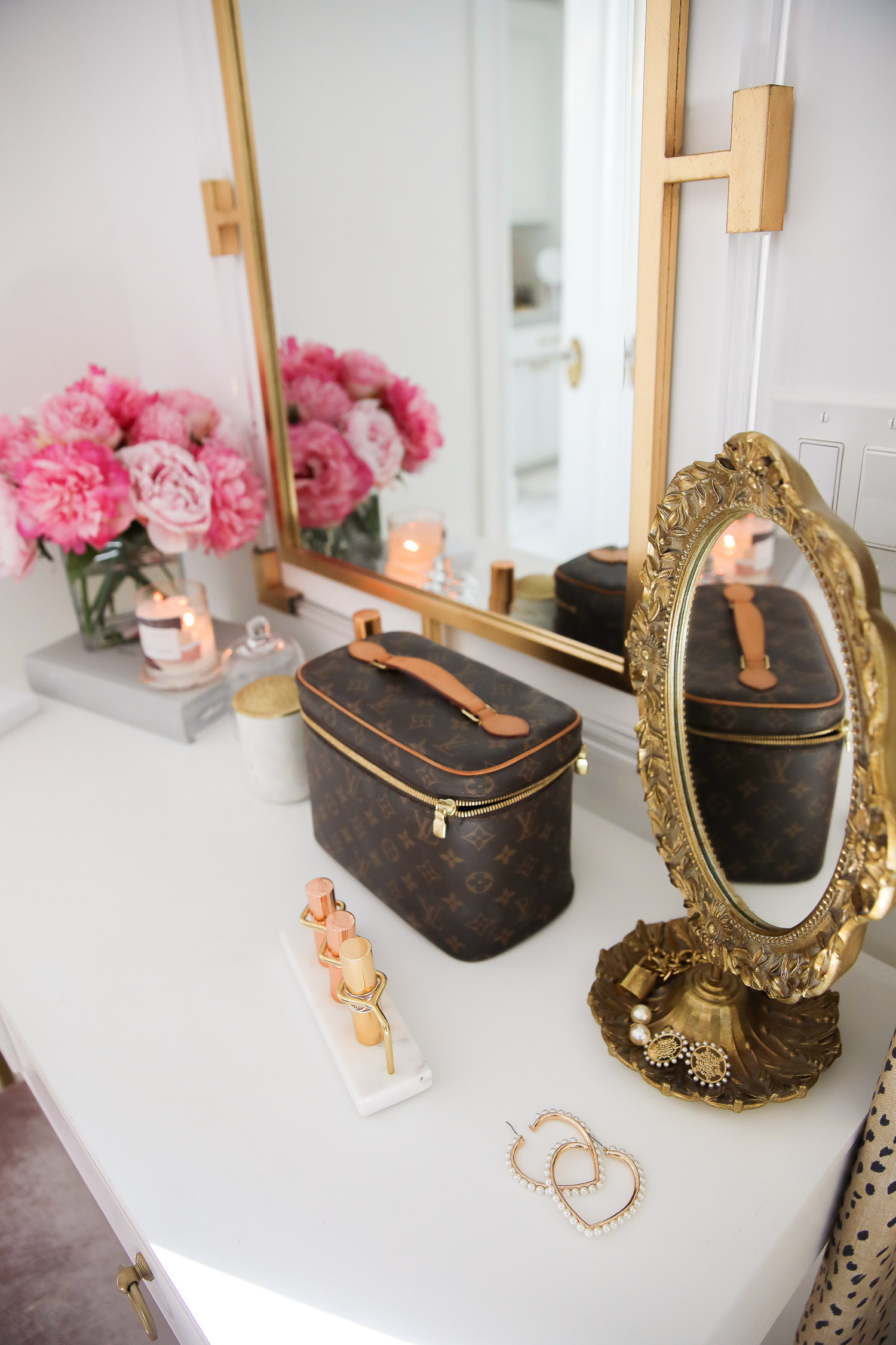 Work From Home Outfits by popular US fashion blog, The Sweetest Thing: image of a vanity with a vase of pink roses, marble and gold lipstick organizer, pearl heart shape earrings, and Louis Vuitton makeup case.