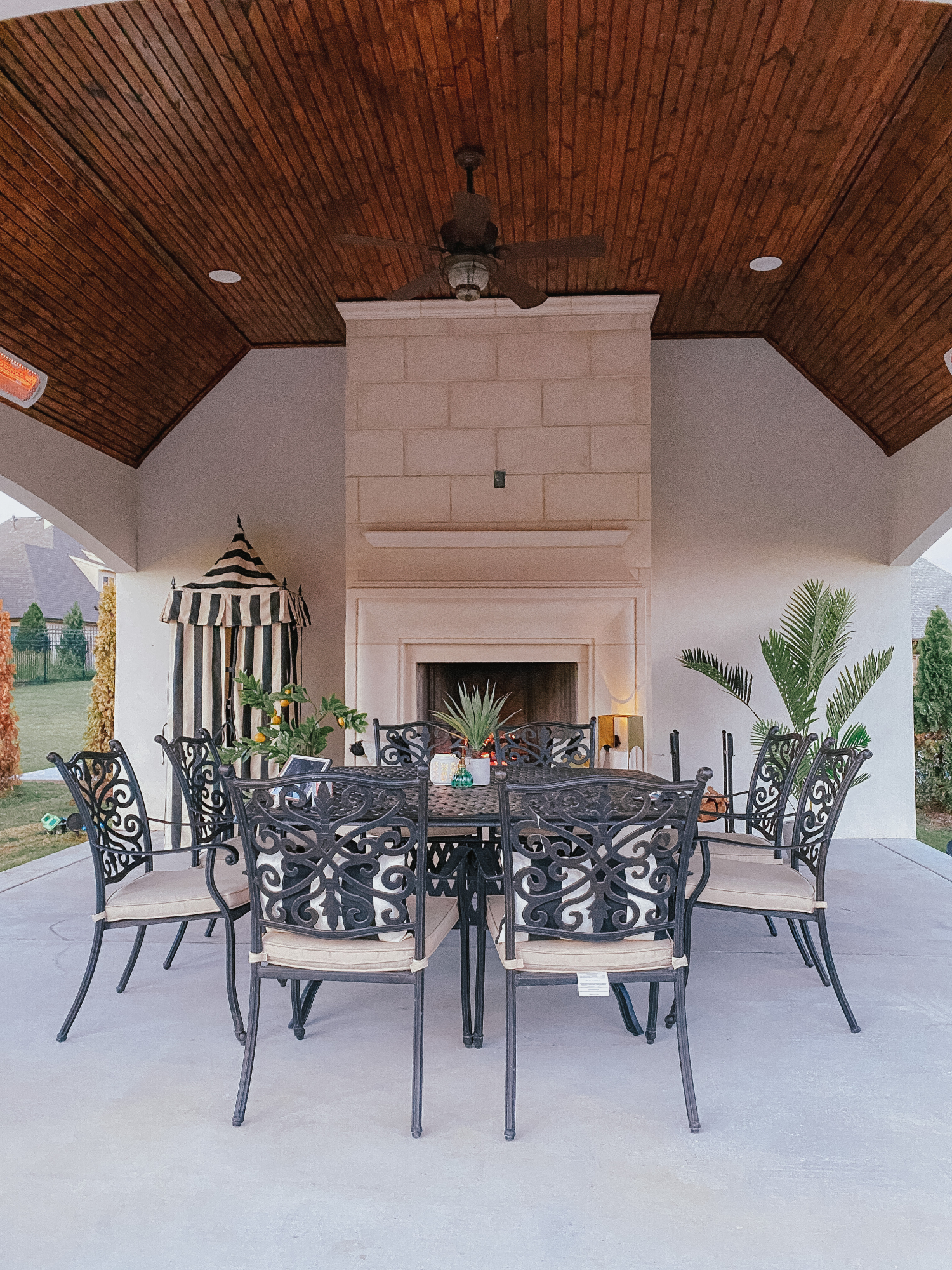 Backyard Decor by popular US life and style blog, The Sweetest Thing: image of a black metal outdoor table and chairs, faux palm tree plant, fireplace, metal log holder, faux yucca plant, faux lemon tree, black and white tent, and gold lanterns.