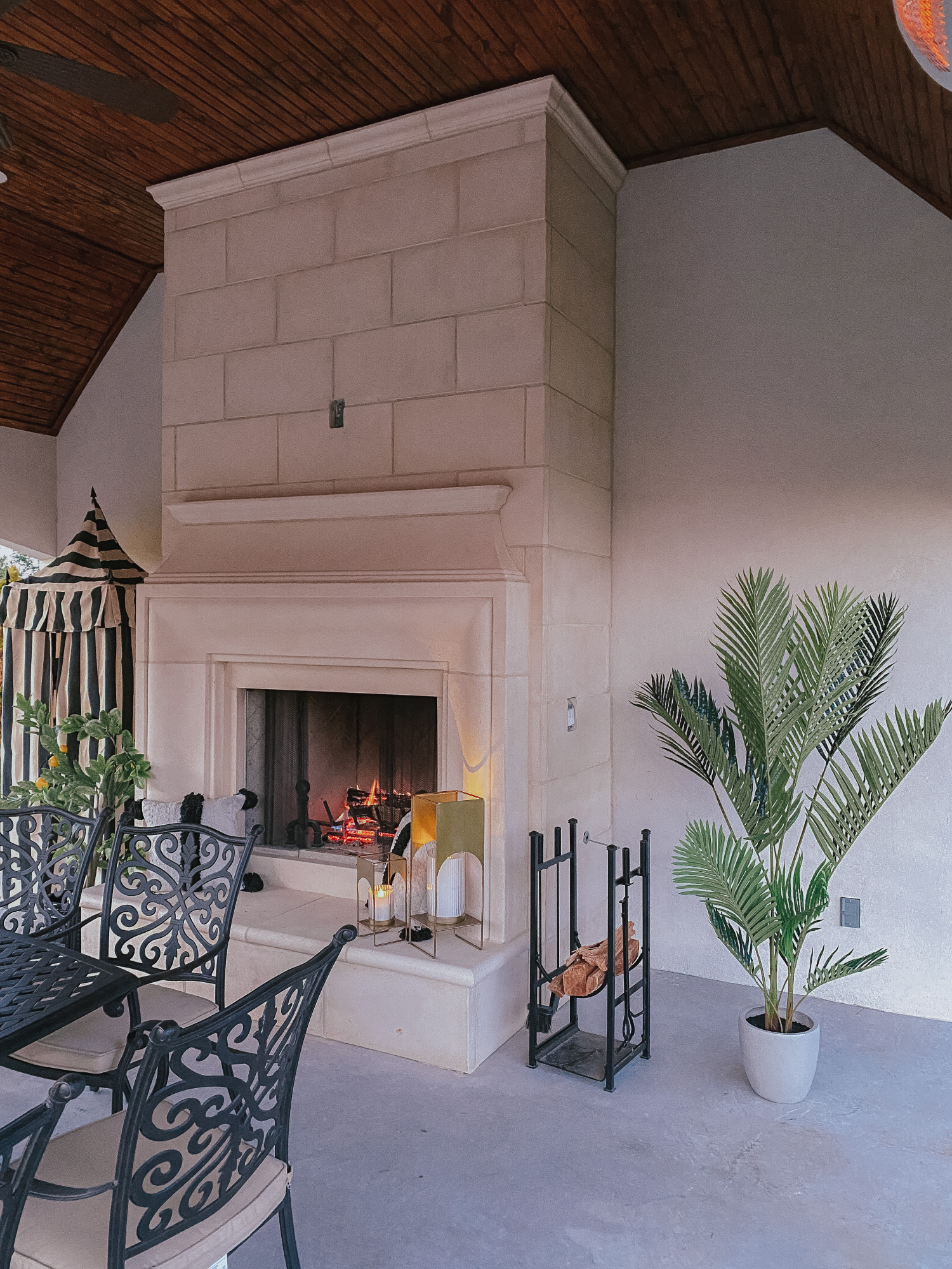 Backyard Decor by popular US life and style blog, The Sweetest Thing: image of a black metal outdoor table and chairs, faux palm tree plant, fireplace, metal log holder, and gold lanterns.