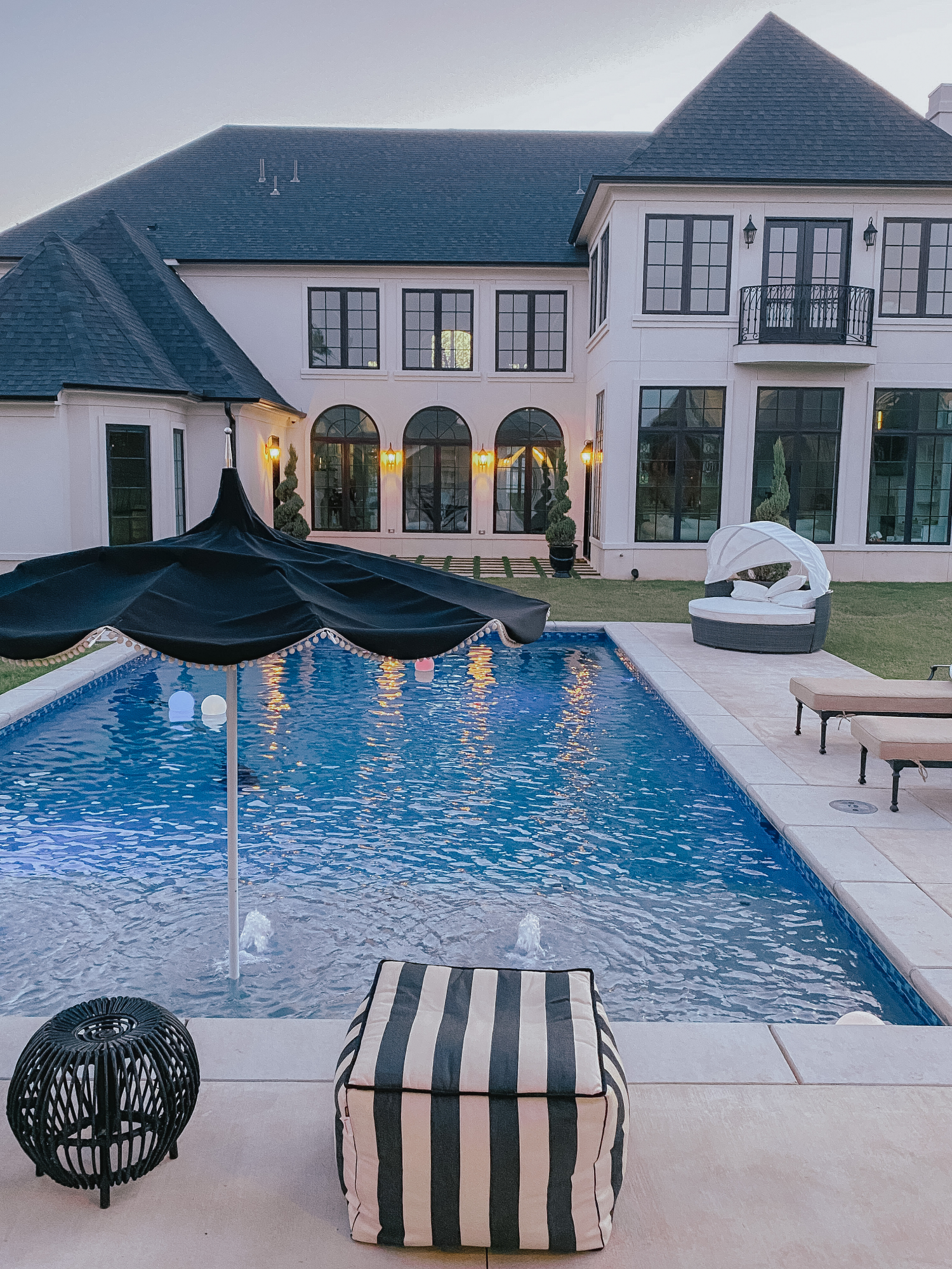 Backyard Decor by popular US life and style blog, The Sweetest Thing: image of a backyard pool, black and white stripe pouf, floating pool orbs, black umbrella with white pom-pom fringe, black and white strip lumbar pillows, and lounge chairs with tan cushions.